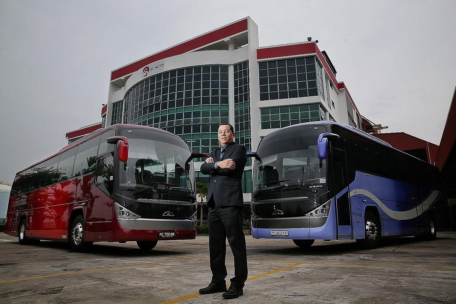 SC Auto chairman Tan Siow Chua with SC Neustar buses, the first to be completely built and designed in Singapore, at SC Auto's Senoko premises. The firm is able to deliver around 900 buses a year from its factories in Senoko and Yangon, Myanmar. Mr T