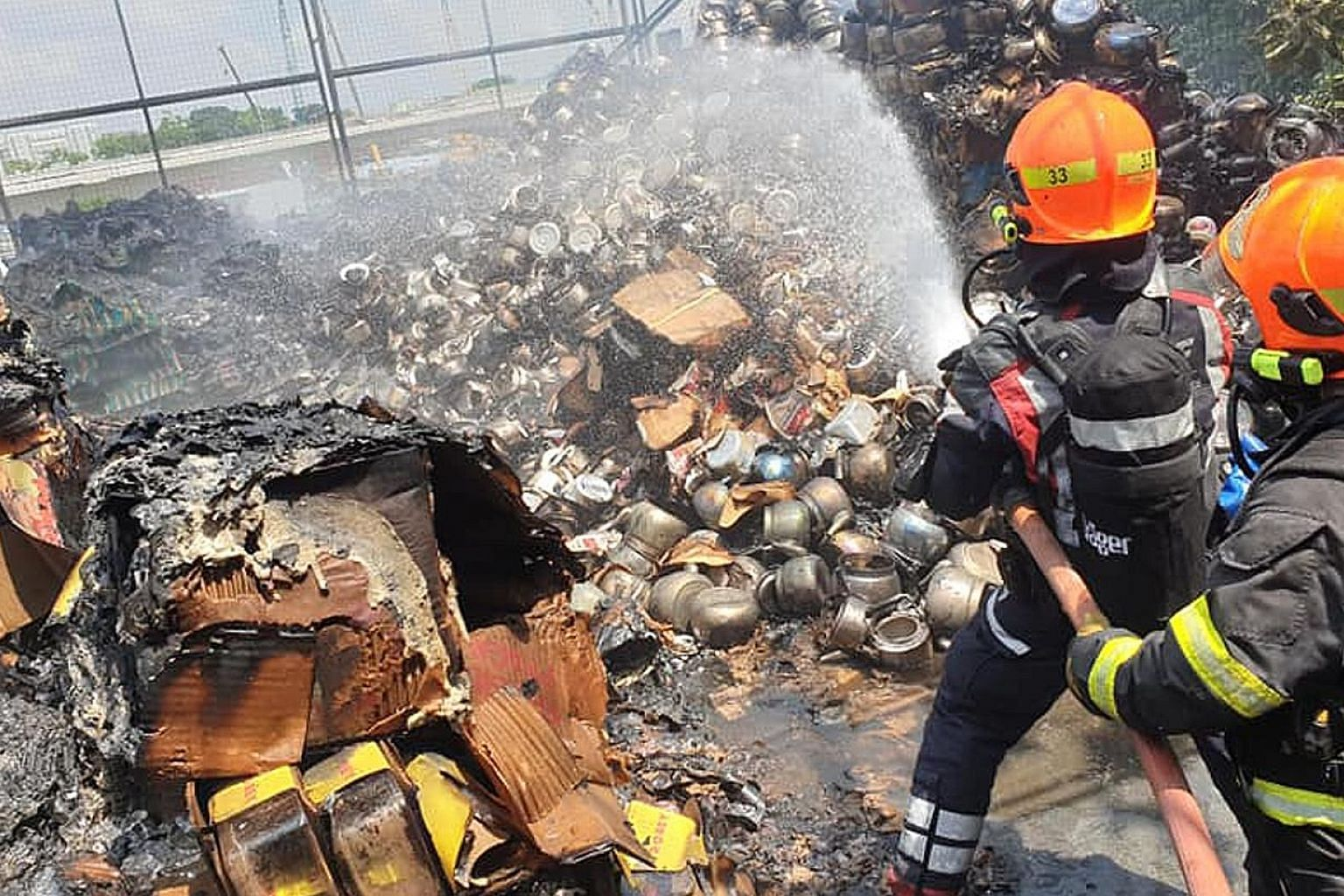 Singapore Civil Defence Force firefighters putting out a fire at 29 Kim Chuan Drive that they were alerted to at about 11.35am yesterday.
