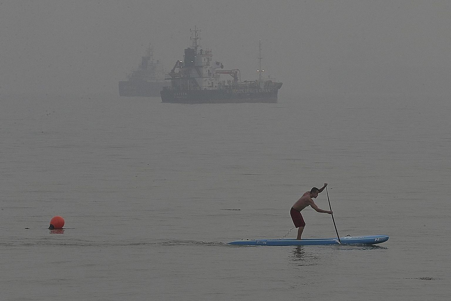 A man, undeterred by the air quality, riding on a paddle board at East Coast Park as the haze partly obscured ships in the distance at around 6pm on Sept 30, 2015.