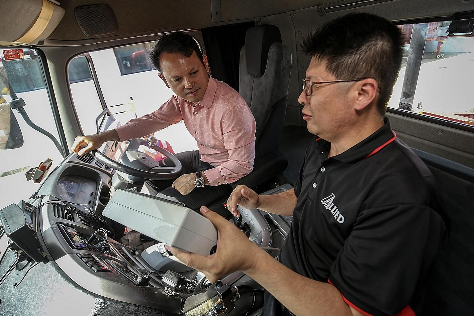 Allied Container Services managing director Lim Kian Chin showing Minister of State for Manpower Zaqy Mohamad how the Auto Quicklock System locks a container onto a trailer without the driver having to leave the cabin.