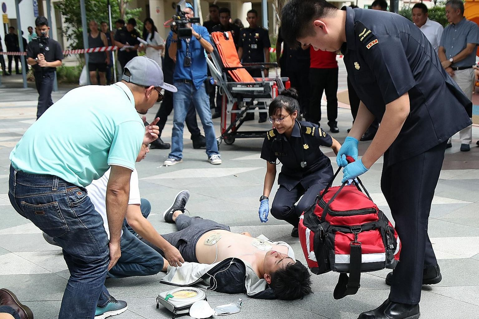 An HDT taxi driver (in light blue cap) and SCDF officers responding to an emergency during a scenario exercise at Kampung Admiralty yesterday, when the HDT Singapore Taxi-Singapore Heart Foundation AED-on-Wheels programme was launched.