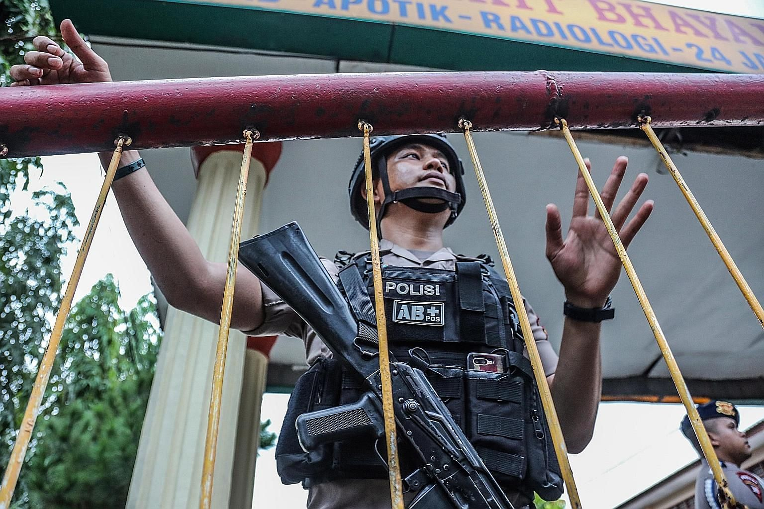 A member of the Indonesian Mobile Brigade Corps guarding the entrance to its headquarters following the killing of the two bomb-makers in a raid last Saturday in Medan, North Sumatra. One police officer was hurt during the raid.