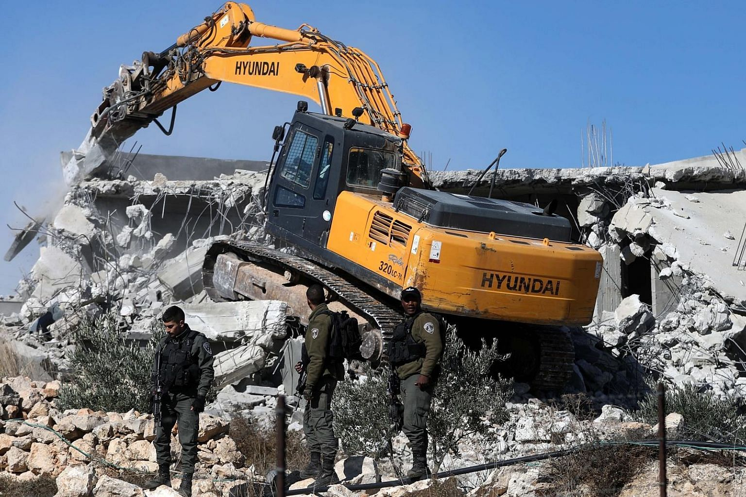 Israeli troops standing guard as bulldozers demolished two houses near Arroub refugee camp north of the West Bank city of Hebron, yesterday. Israel on a regular basis demolishes Palestinians' houses in the West Bank citing missing building permits. P