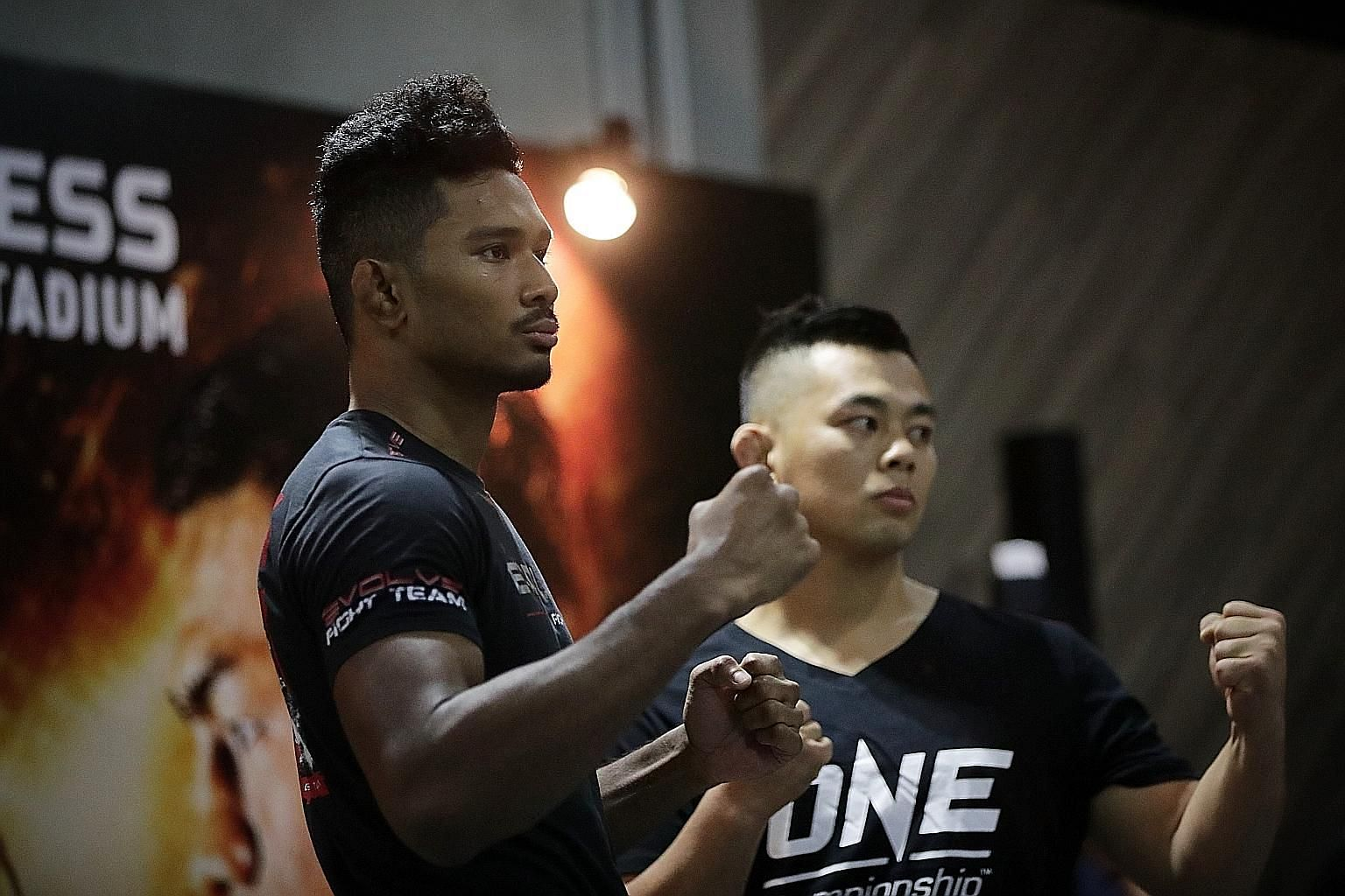 Singapore mixed martial arts fighter Amir Khan (left) was all business yesterday as he faced off with rival Ev Ting at the open workouts ahead of One Championship's Edge of Greatness event. The 25-year-old takes on Malaysian fighter Ting, 30, in the