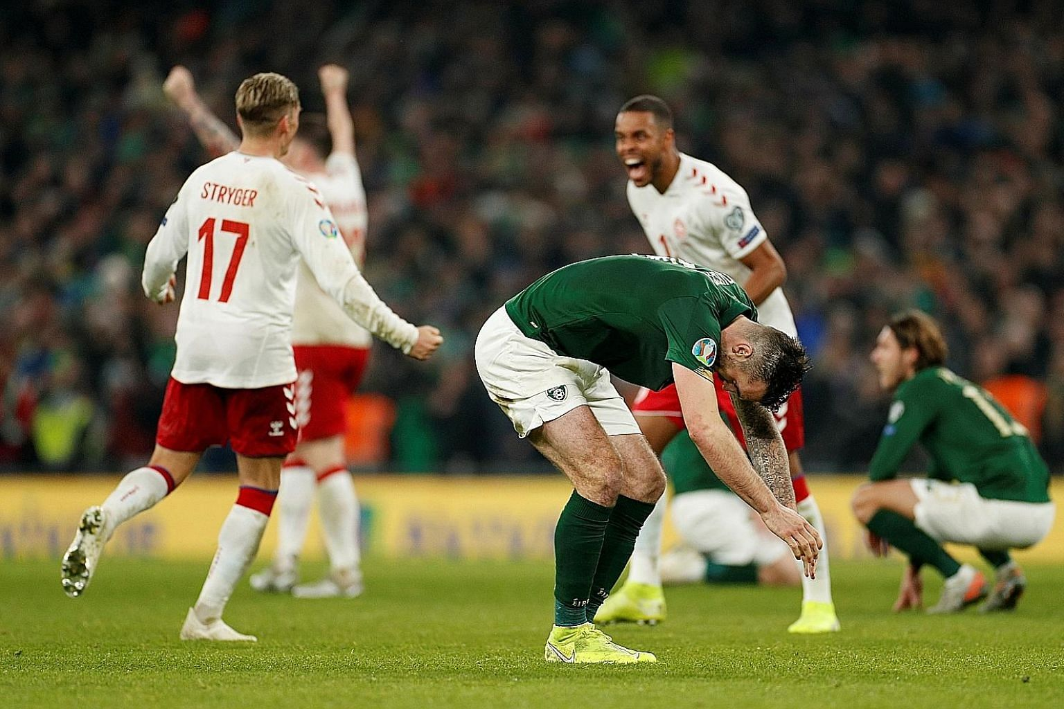 Irish defender Shane Duffy is crestfallen as Denmark's Jens Stryger Larsen and Mathias Jorgensen celebrate at the end of the match in Dublin. An own goal put the visitors ahead and although Matt Doherty equalised, Ireland will have to go through the
