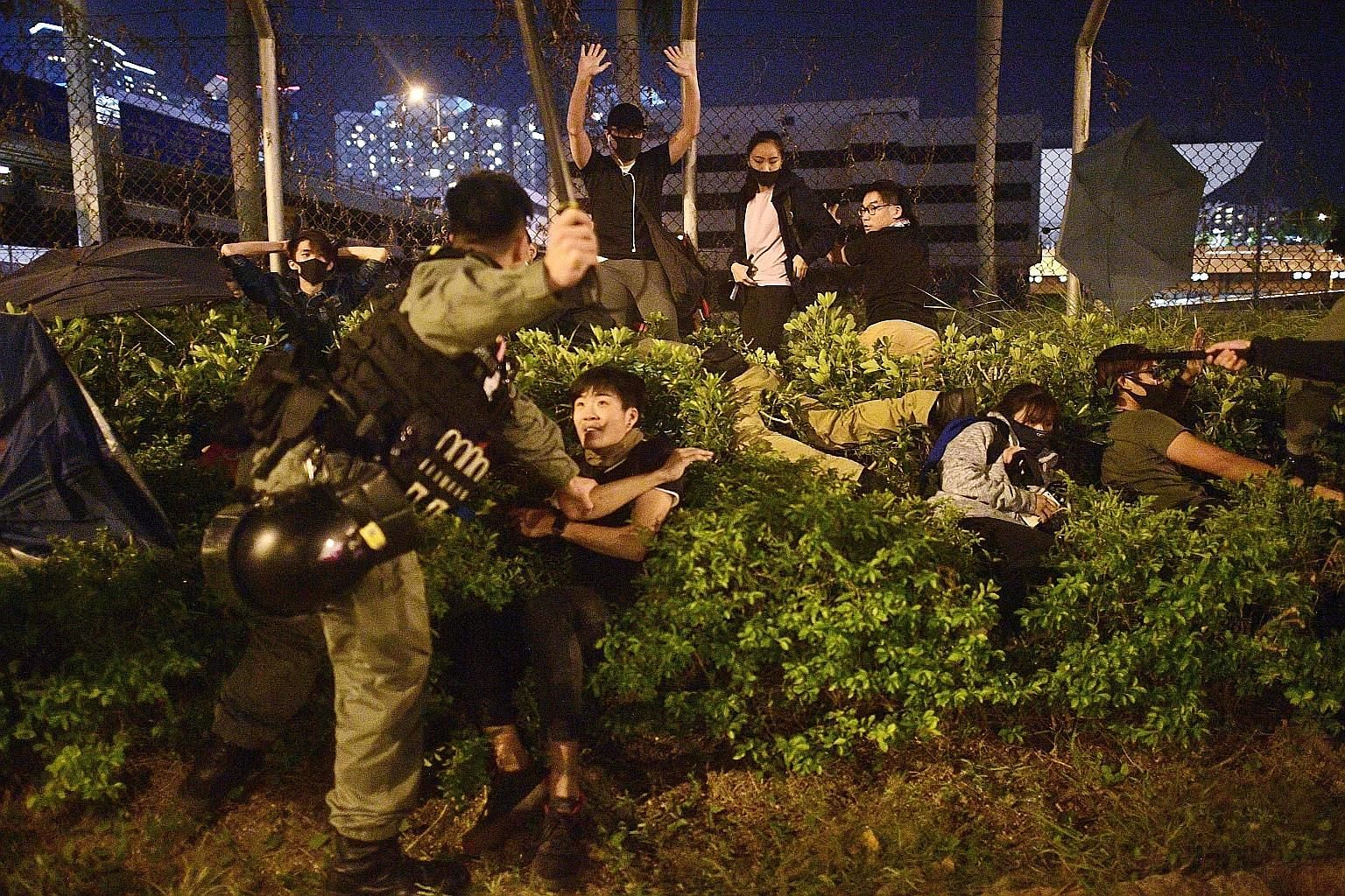 Left: Police detaining protesters trying to flee The Hong Kong Polytechnic University campus yesterday. Right: Protesters waiting to receive medical attention after leaving the campus yesterday. The city's Hospital Authority said 235 injured were tak