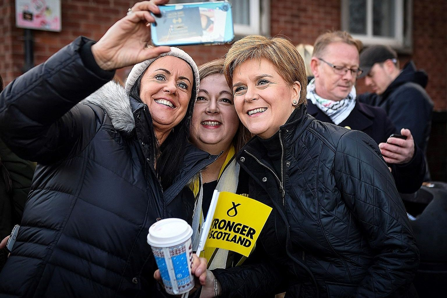 Scottish National Party (SNP) leader Nicola Sturgeon (third from far left) with supporters in Glasgow, Scotland, on Sunday. Ms Sturgeon told voters that a vote for the SNP is a vote to escape Brexit. PHOTO: AGENCE FRANCE-PRESSE