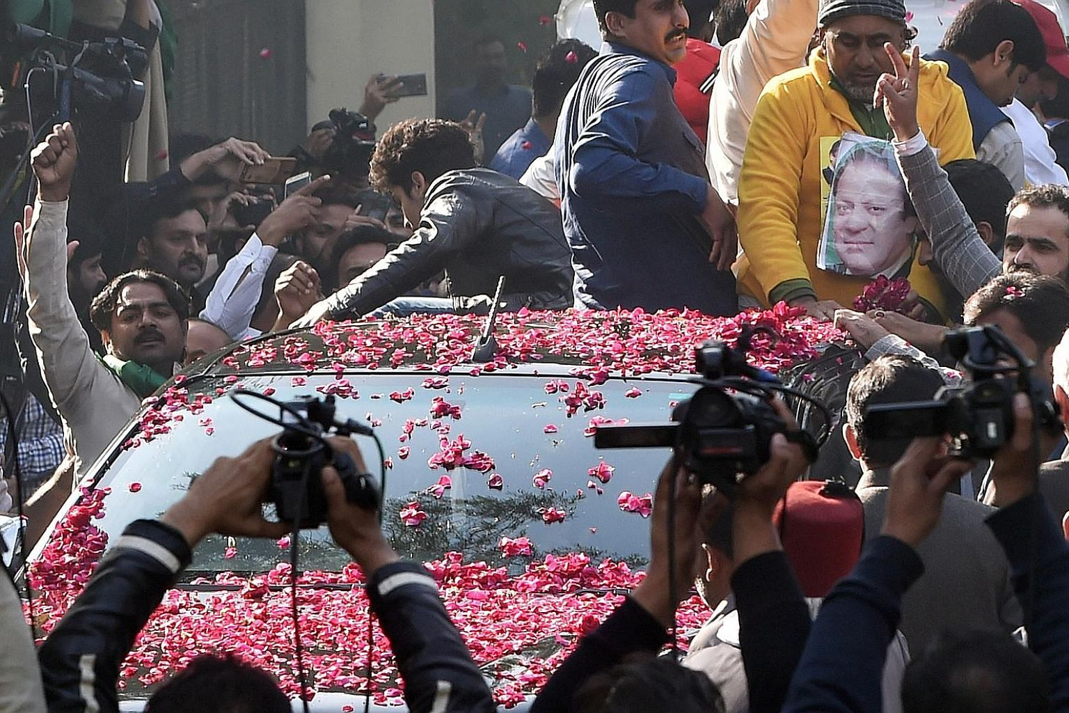 Supporters of Pakistan's former prime minister Nawaz Sharif surrounding his car in Lahore on Sunday. Sharif, who has been sentenced to seven years' jail for corruption, left the country yesterday to receive medical treatment in London, and was allowe