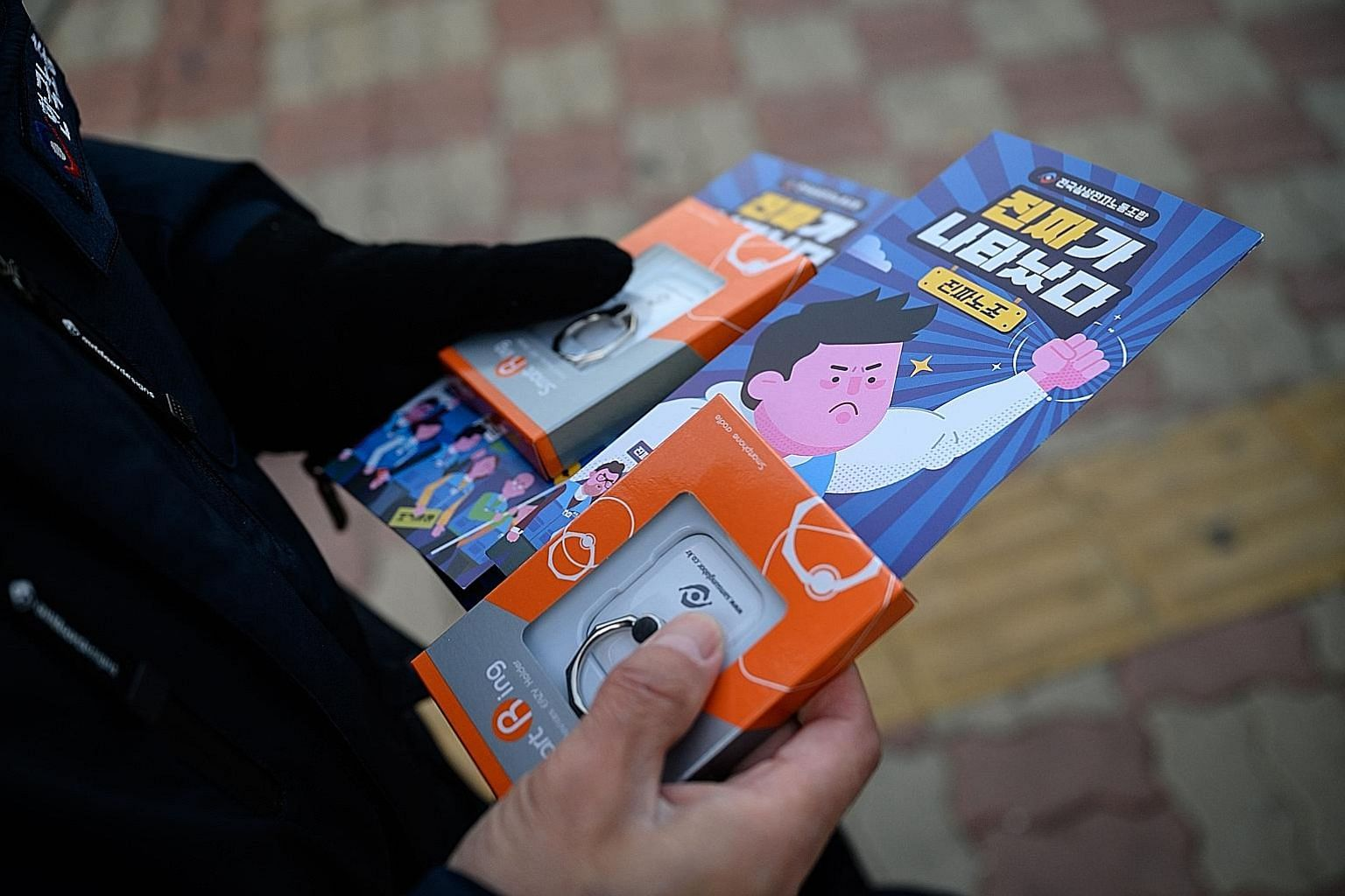 A Samsung Electronics worker holding trade union membership recruitment leaflets. For almost 50 years, the flagship subsidiary of the giant Samsung Group has avoided unionisation of its employees.