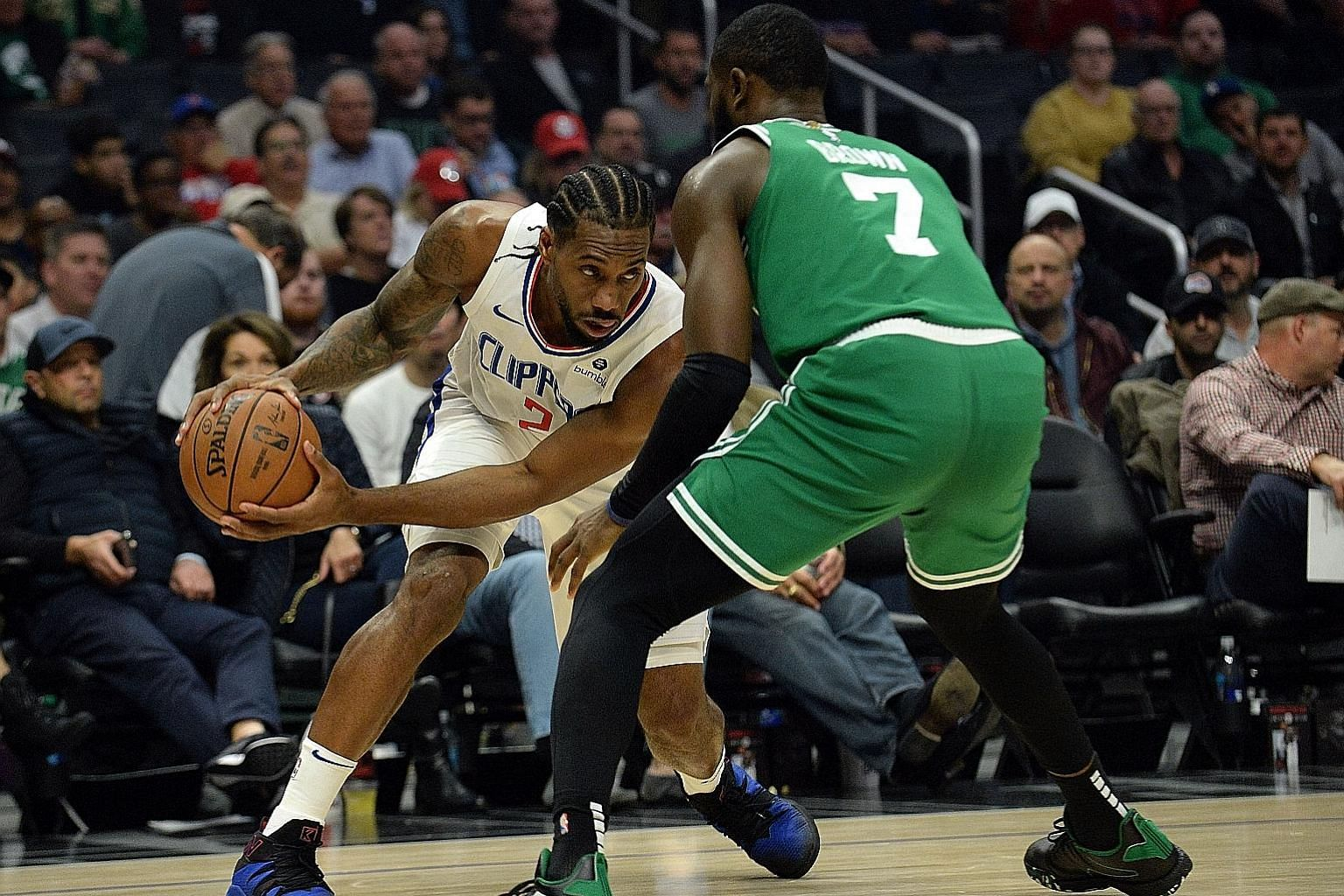 Left: Los Angeles Clippers forward Kawhi Leonard, last season's NBA Finals Most Valuable Player, goes up against Boston Celtics guard Jaylen Brown during the Clippers' 107-104 overtime win on Wednesday night. Below: Clippers forward Paul George shoot