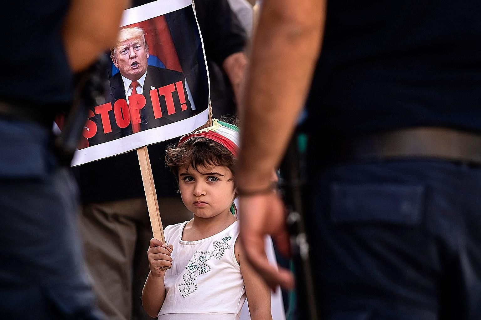 A girl in Cyprus with a placard of US President Donald Trump last month in a protest against the Turkish offensive into Syria. While some feel Mr Trump's departure would set the US and the world on a path back towards some idea of normal, the writer