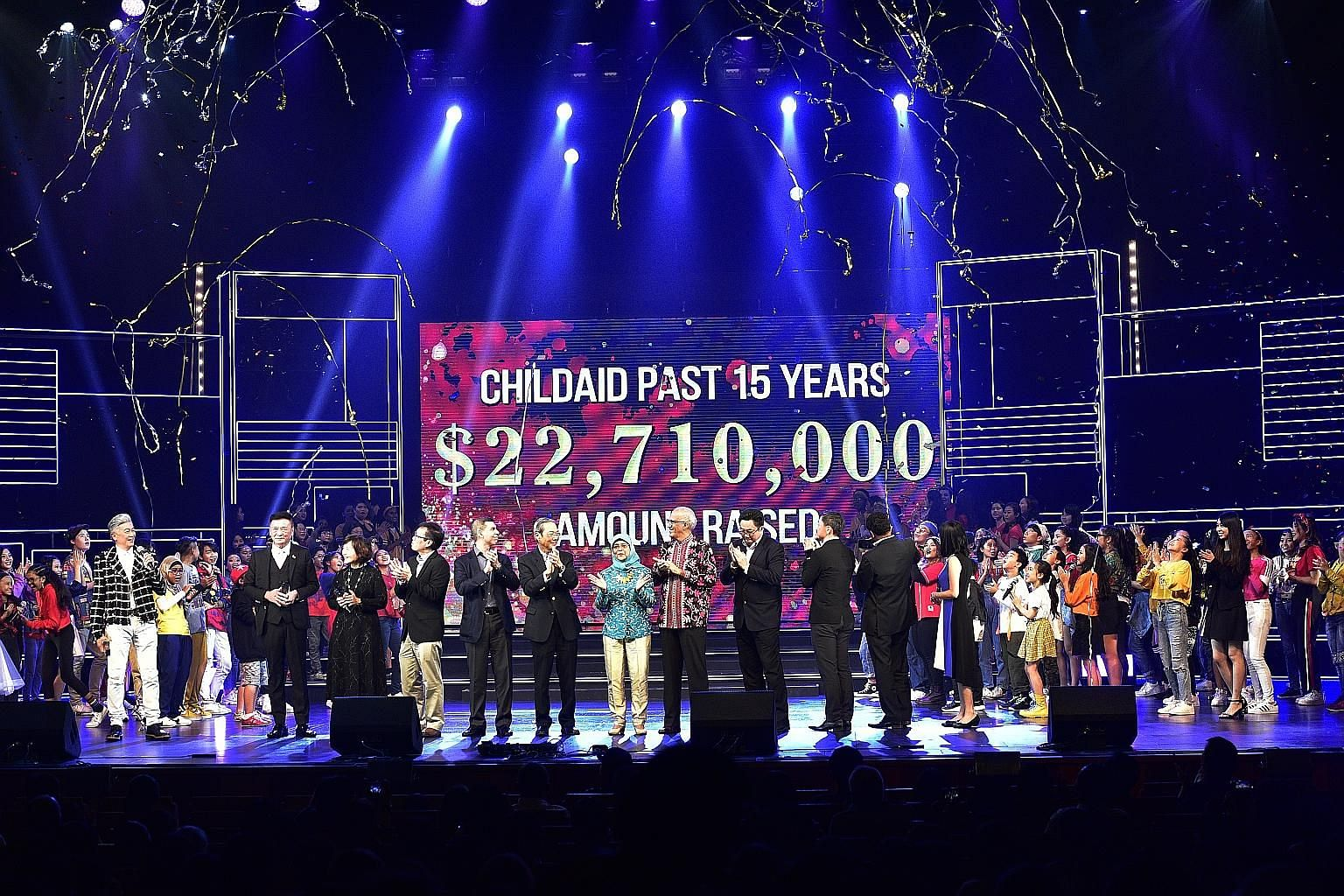 President Halimah Yacob and her husband, Mr Mohamed Abdullah Alhabshee, at the ChildAid 2019 event which raised $2.12 million for charity this year. With them on stage last night were the show's performers, its creative director Dick Lee, Singapore P