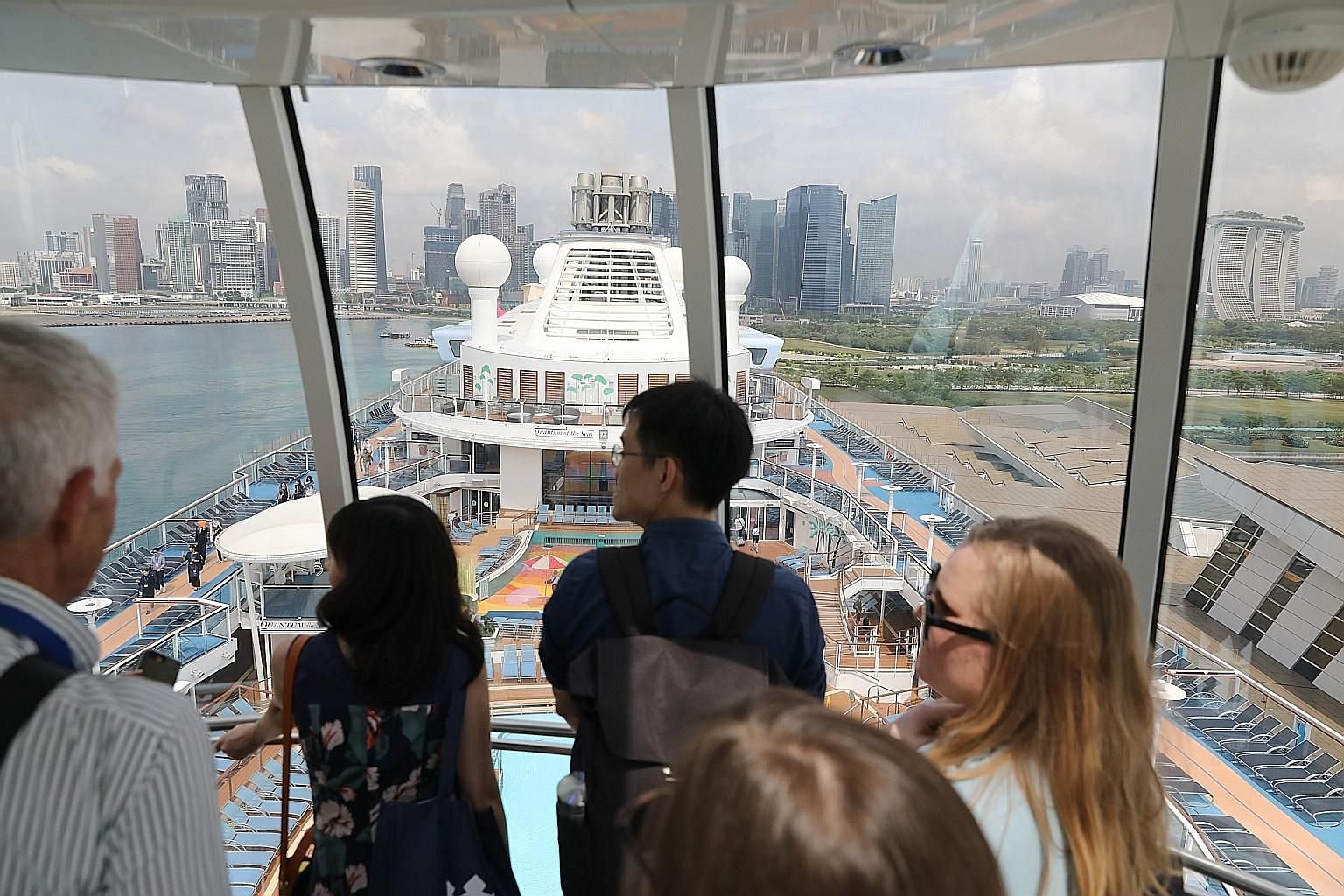 Passengers on board Quantum Of The Seas taking in views of the Singapore skyline from North Star, an observational capsule that offers 360-degree views.