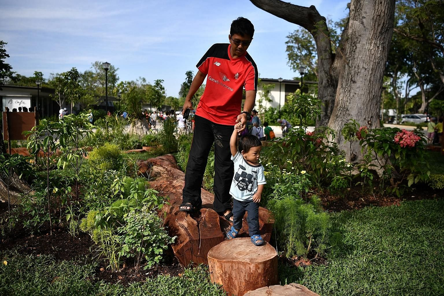 Mr Ahmad Abdillah and his 1½-year-old son Ahmad Khairi at the nature play garden yesterday. In order to provide natural shade and vibrancy, 800 trees have been planted at the new Cyclist Park.