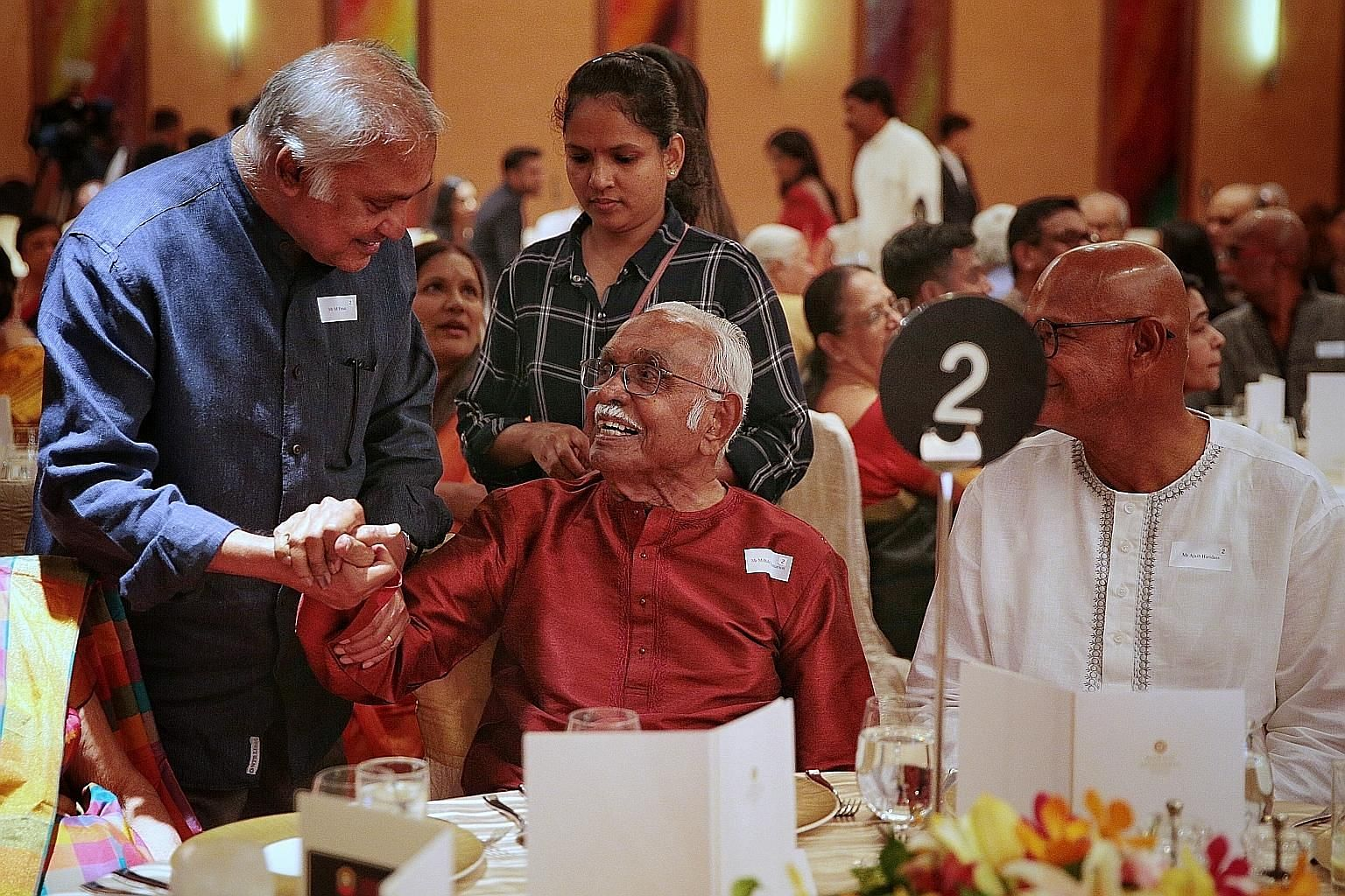 Mr Bala Subramanion, 102, Singapore's first Asian postmaster-general, being greeted by Mr M. Param (left), former vice-chairman of the Hindu Endowments Board, during last night's dinner at the Marina Mandarin hotel to mark the board's 50th anniversar