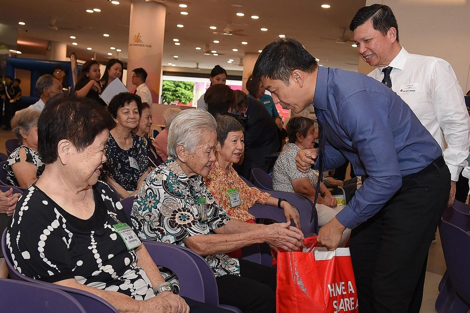 Speaker of Parliament Tan Chuan-Jin distributing food hampers to elderly beneficiaries at the launch of the 2019 Boys' Brigade Share-a-Gift charity drive at Our Tampines Hub.