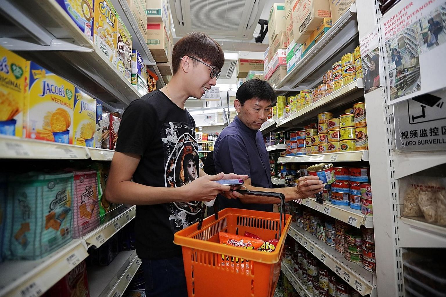 Mr Lee Jong Ren, 29, a retail sales assistant going through a shopping list with Senior Minister of State for Trade and Industry and Education Chee Hong Tat yesterday at Kim Eng Mini Supermarket in Chong Pang City. A four-year plan has been created t