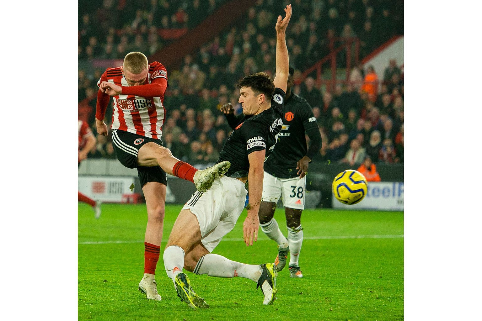 Sheffield United's Oli McBurnie beating Manchester United defender Harry Maguire to the ball to make it 3-3 in the 90th minute in their English Premier League match at Bramall Lane on Sunday. PHOTO: EPA-EFE