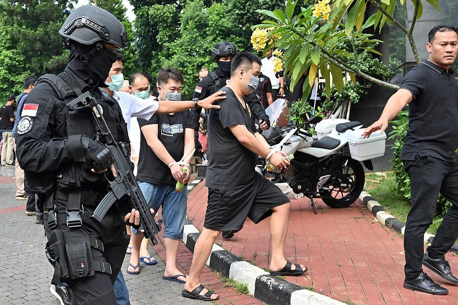 Indonesian police escorting a group of Chinese and Indonesian suspects in Jakarta yesterday. Dozens of Chinese nationals and six Indonesians were arrested over an online scam that bilked victims out of millions of dollars after the Indonesian police