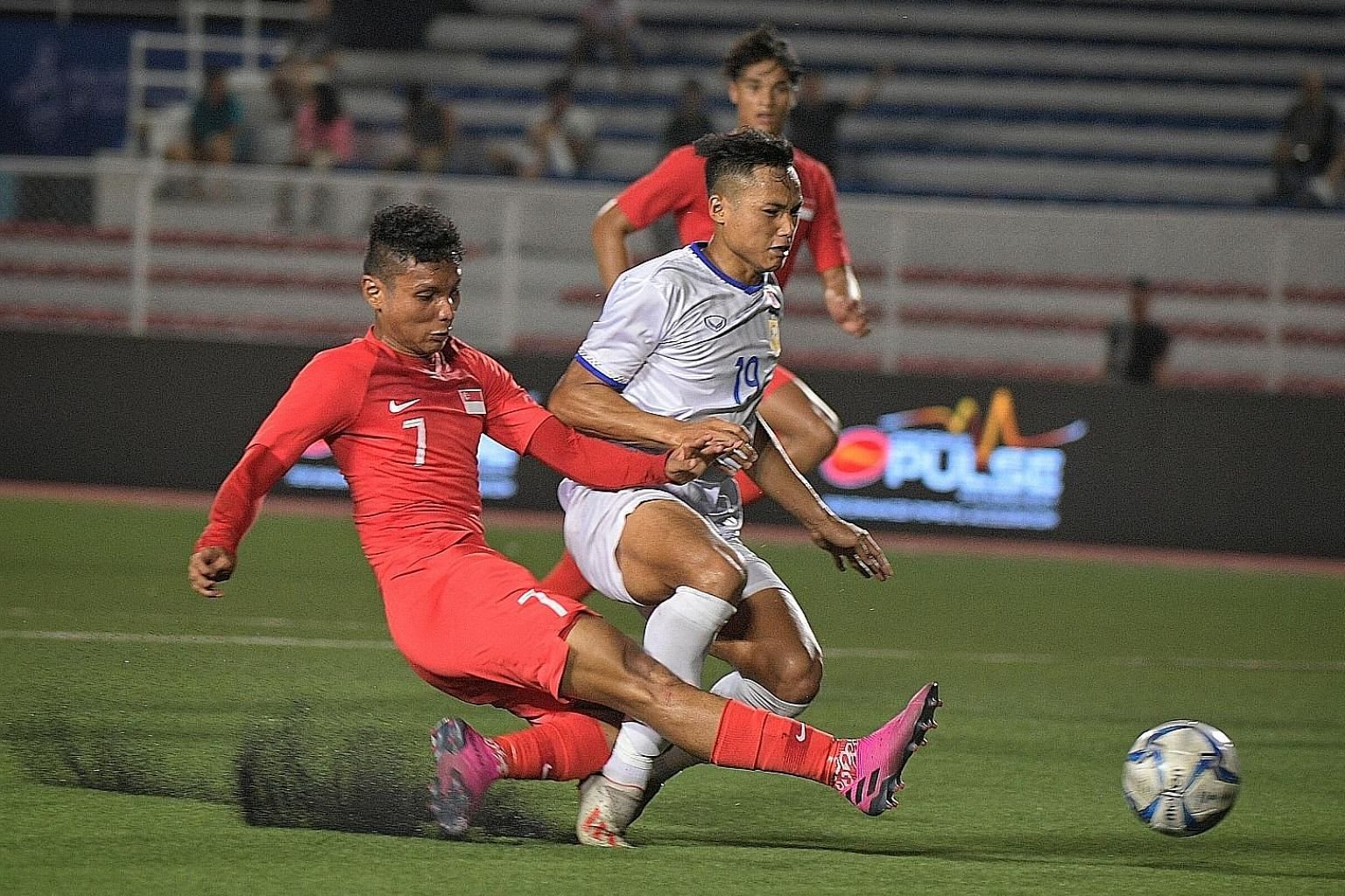 Left: Singapore's Zulqarnaen Suzliman getting in a shot against Laos in their SEA Games Group B opener at the Rizal Memorial Stadium in Manila. Below: Laos coach V. Sundram Moorthy is clearly the happier of the two as he shakes hands with Singapore c