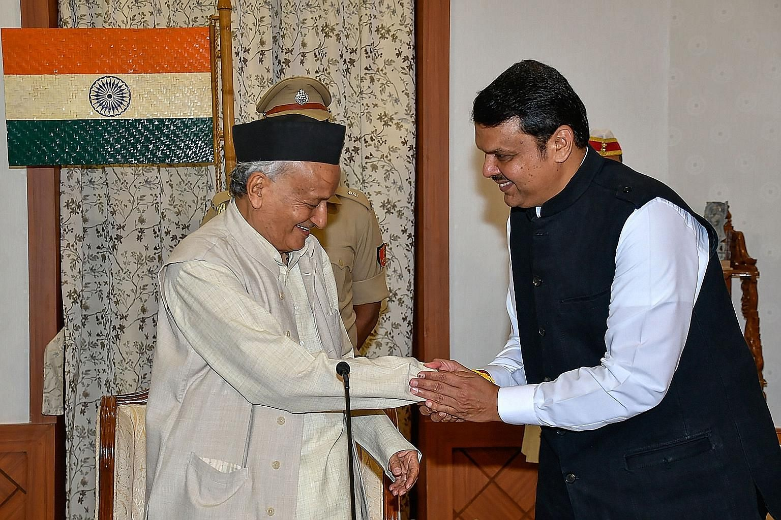 Maharashtra Governor Bhagat Singh Koshyari (left) greeting BJP's Devendra Fadnavis after his swearing-in as chief minister last Saturday. Mr Fadnavis resigned from his post yesterday.