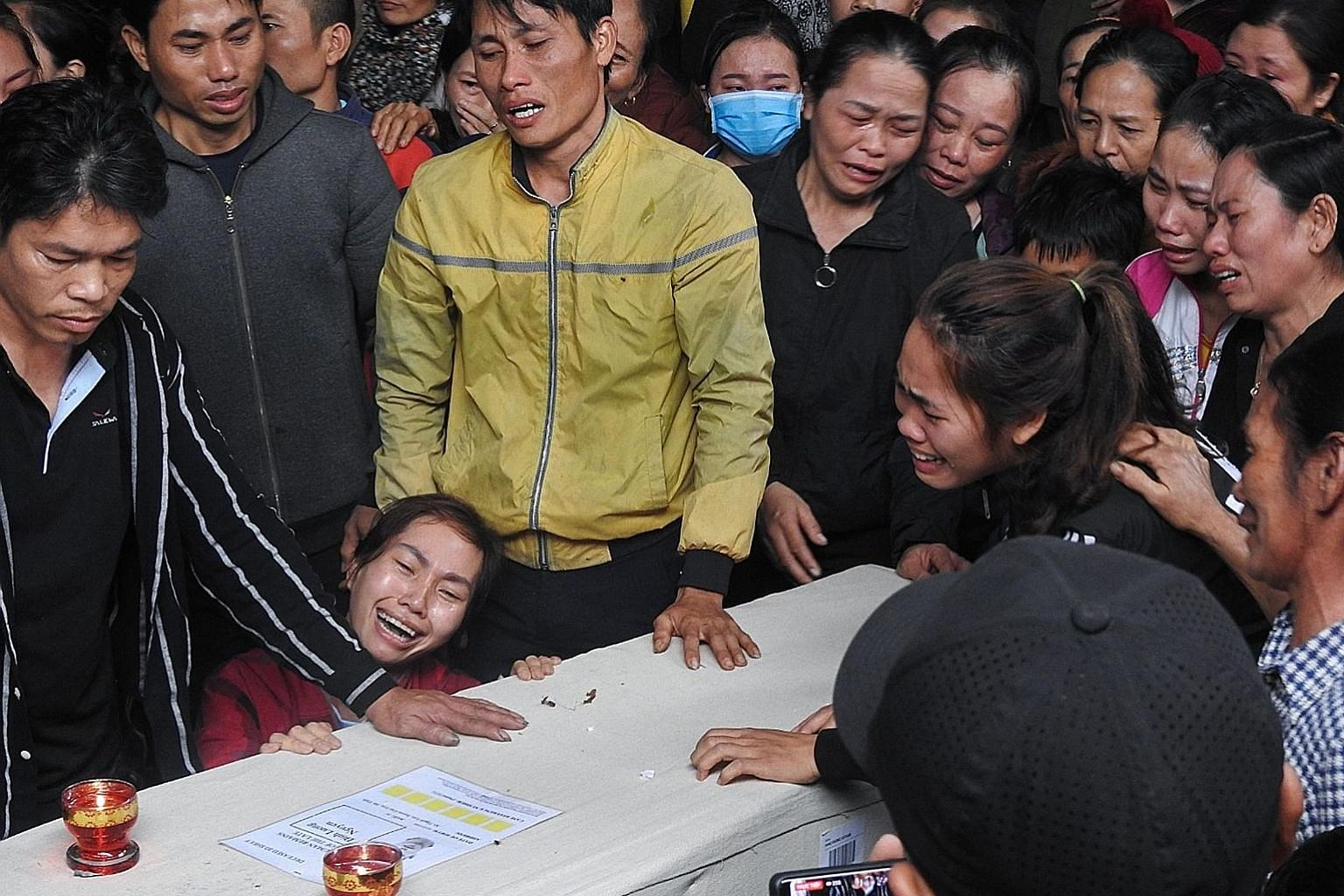 Relatives in Vietnam grieving over the repatriated remains of Mr Nguyen Dinh Luong, 20, who died in the back of a truck in Britain.