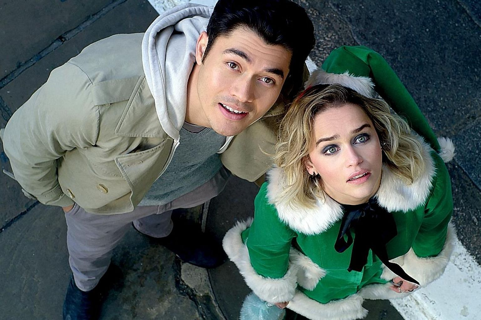 In Last Christmas, Emilia Clarke's character Kate, who hates her job working as an elf in a year-round Christmas shop, meets Tom (Henry Golding, both left) and is prodded into looking at the world differently.