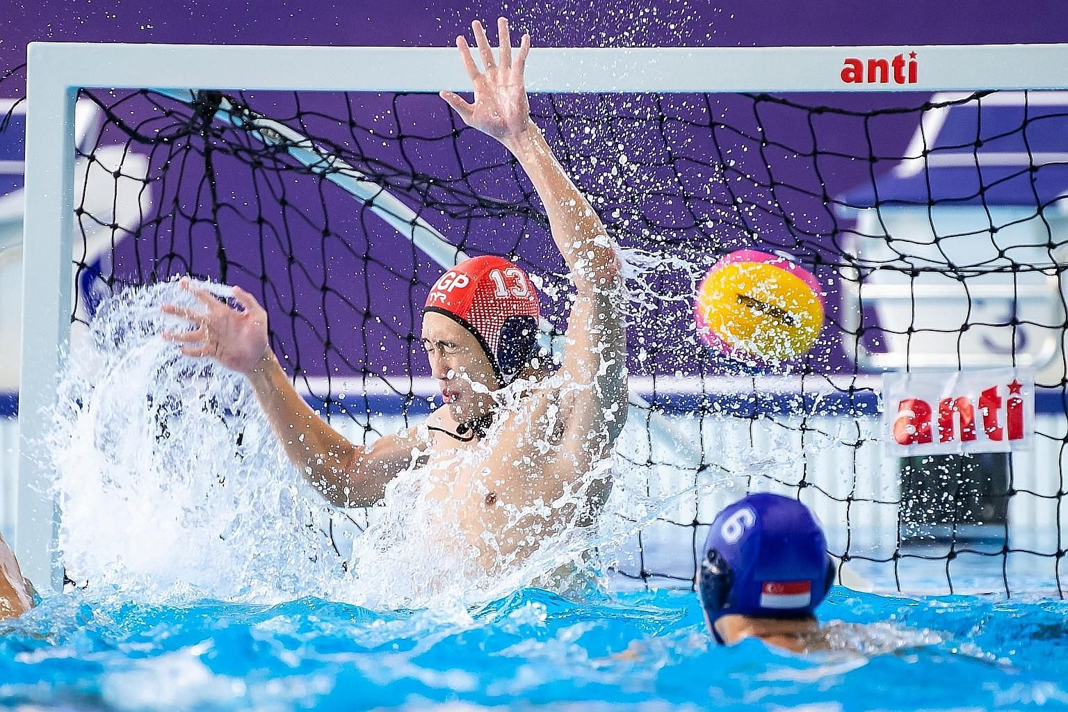 Left: The Singapore team were crestfallen after their first-ever defeat in the competition. Below: Singapore goalkeeper Lee Kai Yang is helpless to prevent one of the seven goals scored past him by the Indonesian team, who can seal the gold medal wit