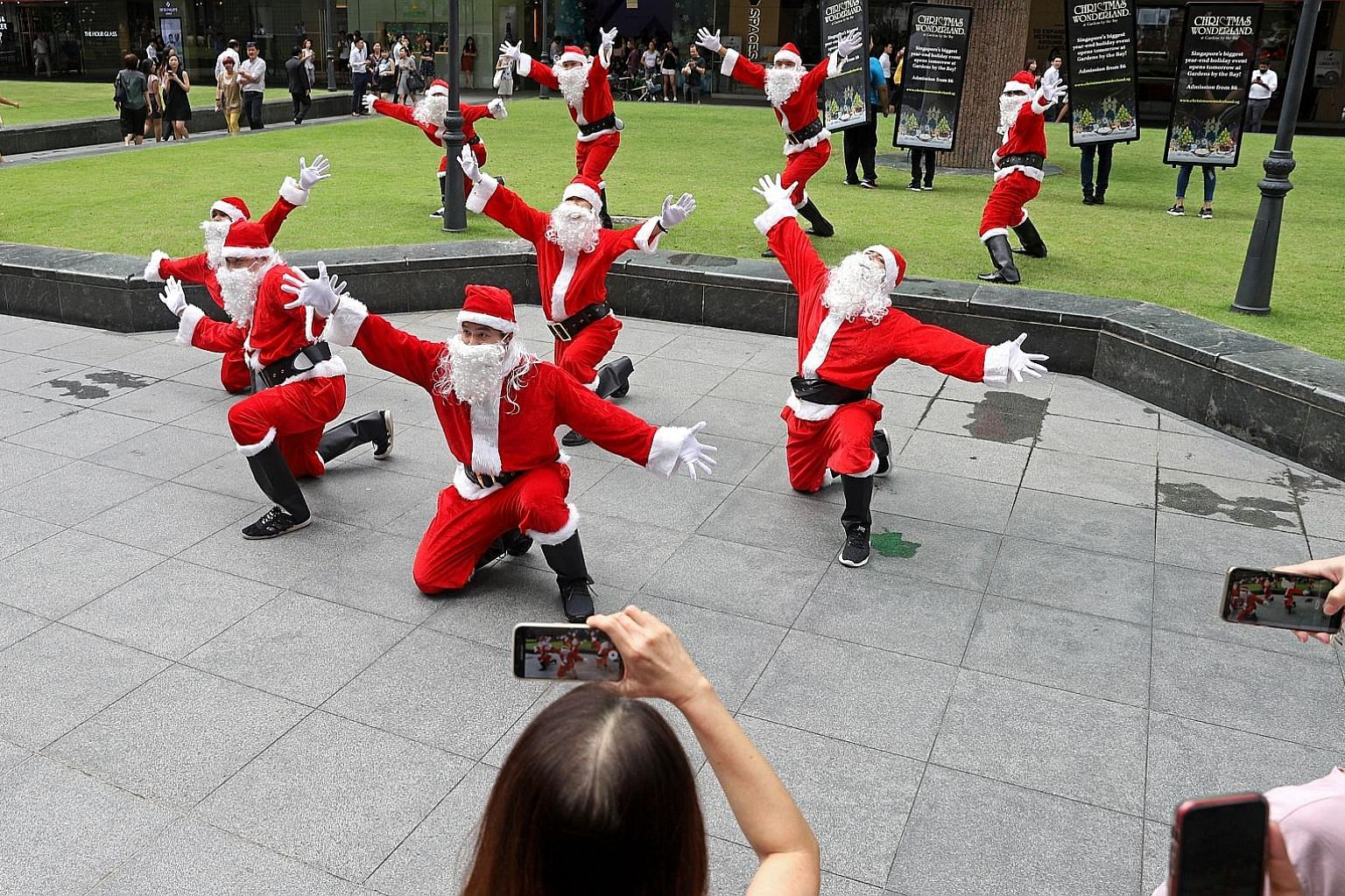 Santas dancing during a flash mob in front of One Raffles Place around 1pm yesterday. There were 10 people in total who were decked from head to toe in Santa Claus outfits to publicise Christmas Wonderland 2019. After the dance, they posed for photos