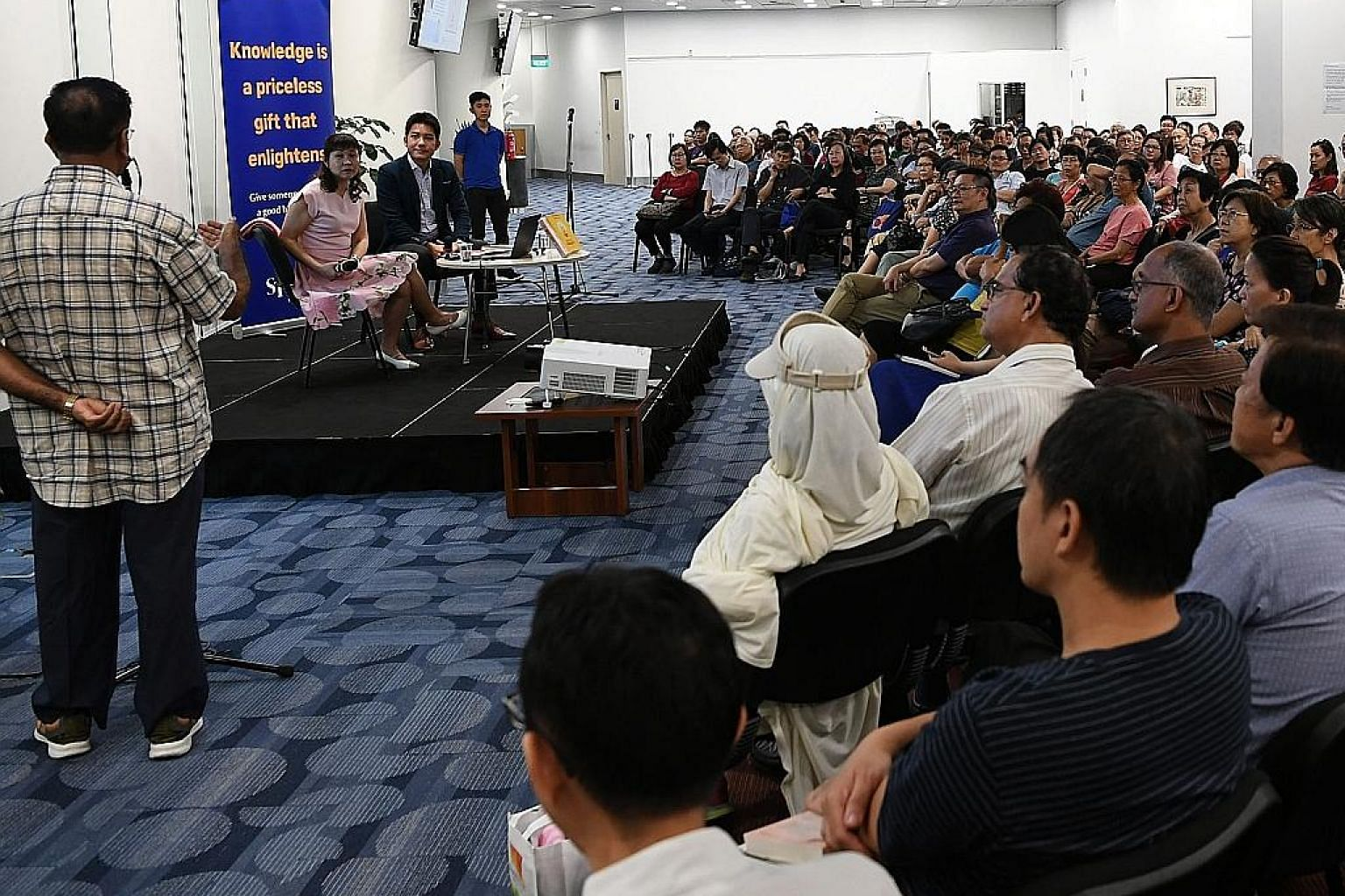 An audience member asking author Lorna Tan a question at her talk. The Straits Times Book Club session was moderated by Money FM 89.3 morning show host Ryan Huang.