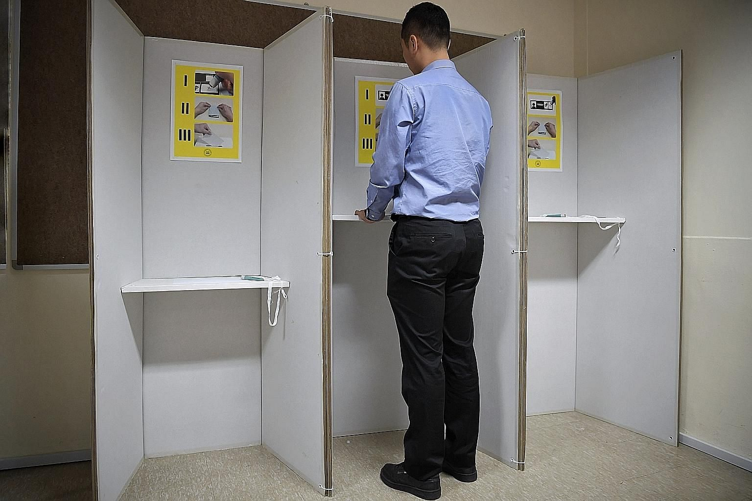 "Above and right: Prototype polling booths made largely from cardboard and other recyclable materials will be used in one GRC and two SMCs. Voters in wheelchairs can use a booth with a lower table. Self-inking pens will allow voters to stamp an ""X"" fo"