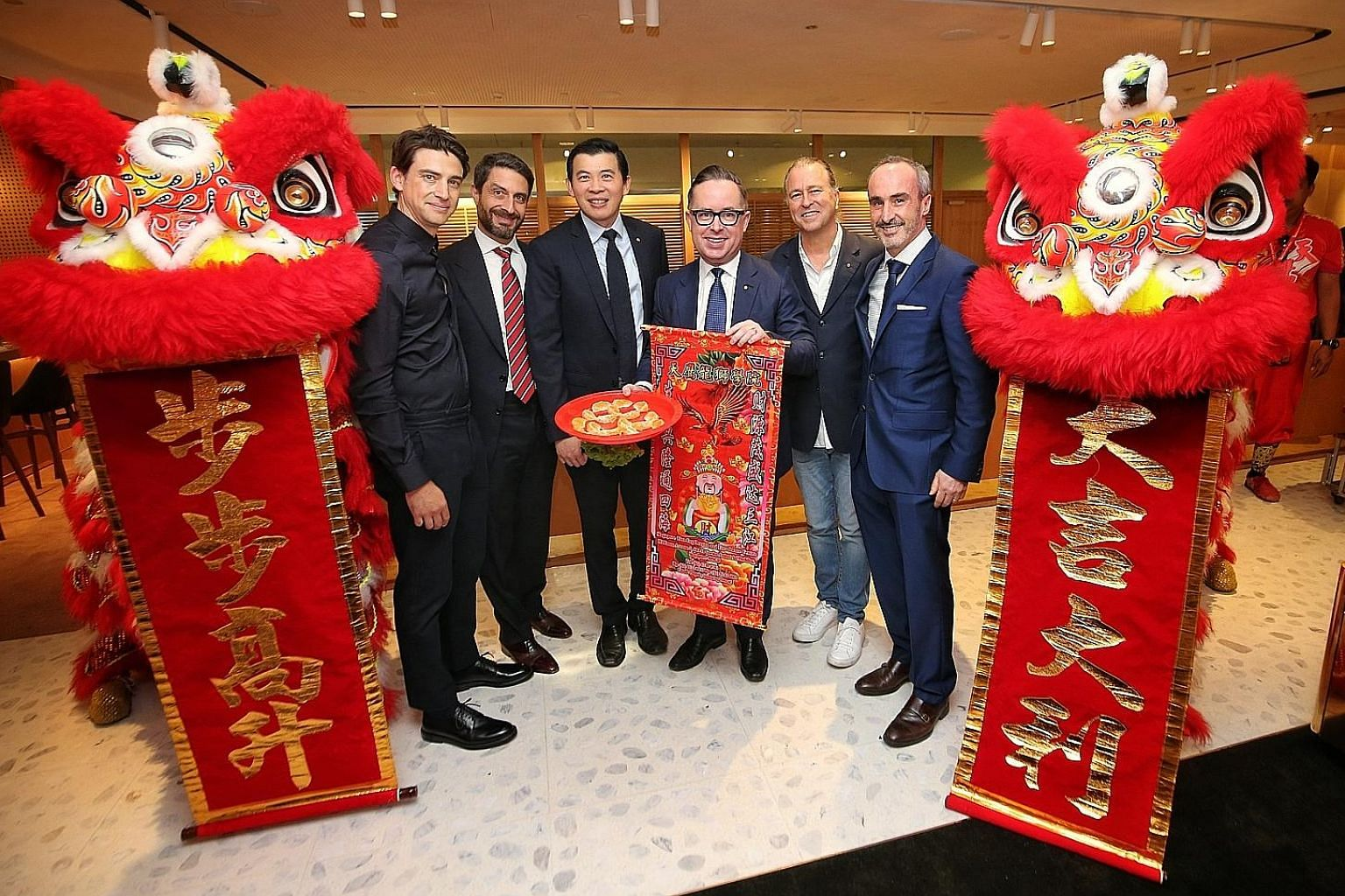 Qantas International chief executive Tino La Spina (second from left), Changi Airport Group chief executive Lee Seow Hiang (third from left) and Qantas chief executive Alan Joyce (with banner) with key designers of Qantas First Lounge at the opening