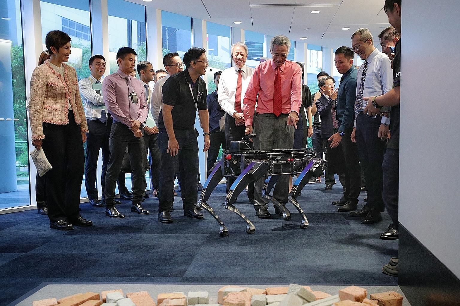 Prime Minister Lee Hsien Loong checking out a Rover-X robotic dog during the launch of the Home Team Science and Technology Agency yesterday, as Mr Ong Ka Hing (in black), deputy director for robotics at HTX's Autonomous Unmanned Systems Centre of Ex