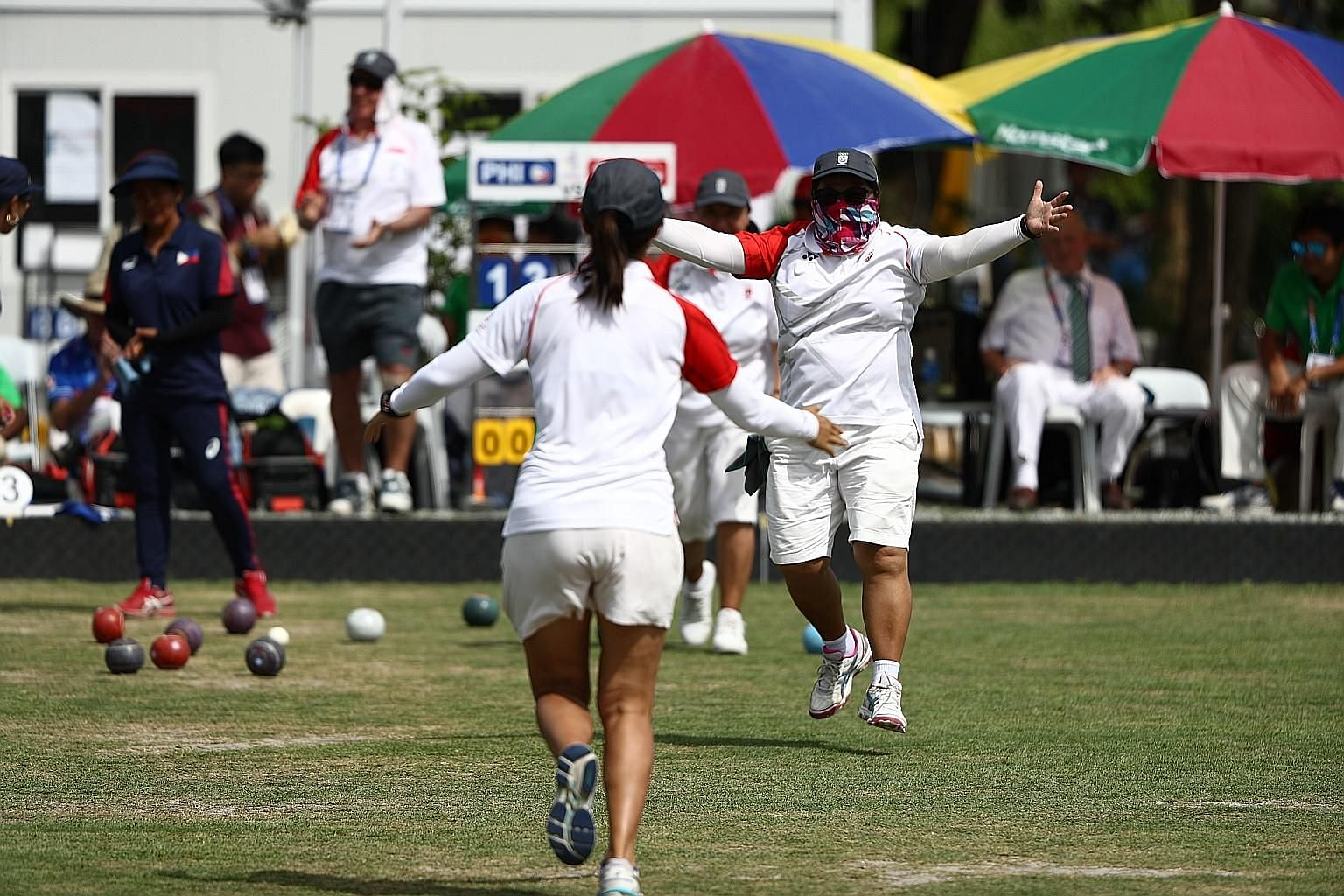 From left: Goh Quee Kee, Lim Poh Eng and Shermeen Lim with their golds beating the Philippines 16-13 in the lawn bowls trio final yesterday. Right: There was relief and joy at the end, with the Republic having trailed 8-11 at the Friendship Gate in C