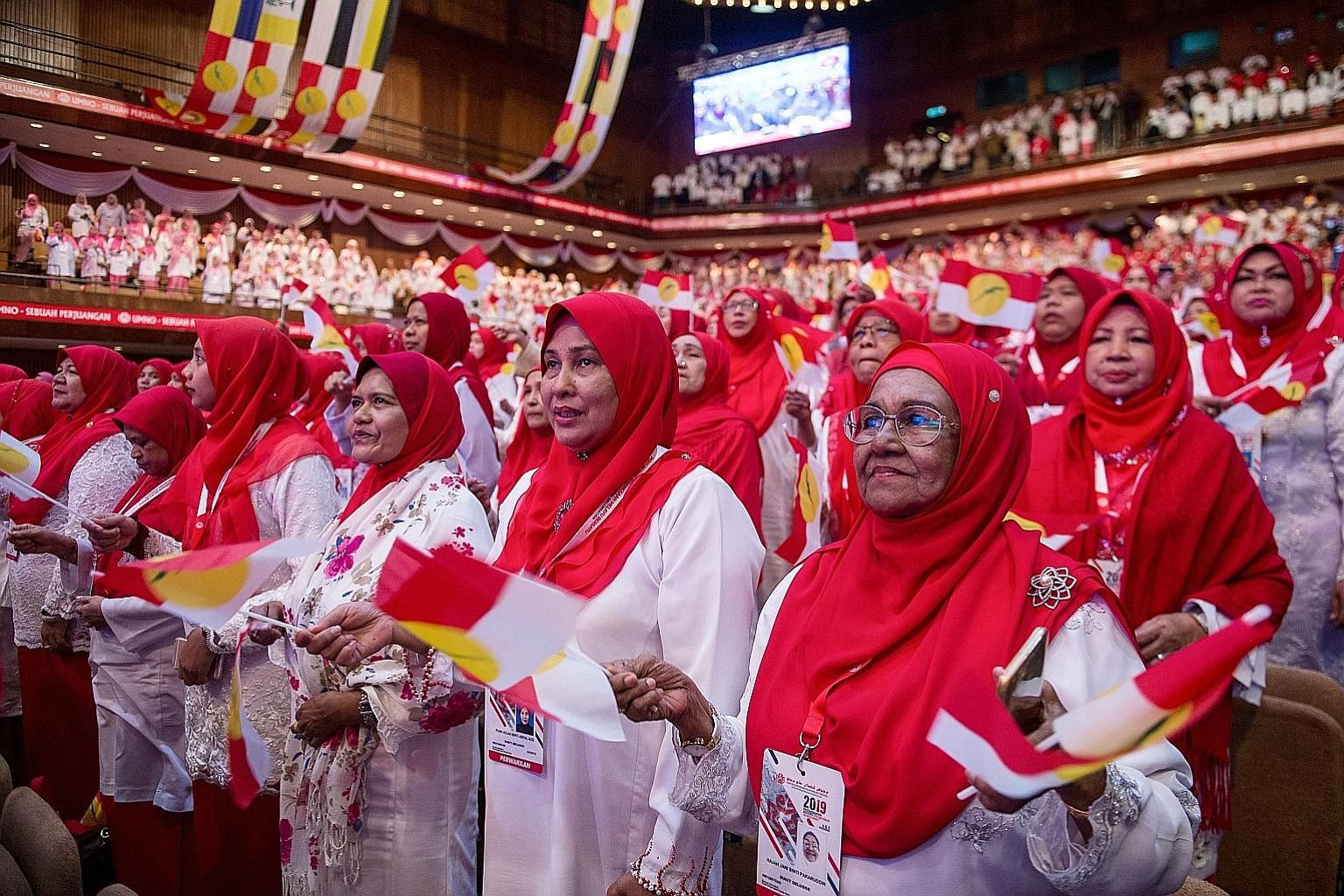 Umno deputy president Mohamad Hasan (in blue) arriving at the opening of the party's Women, Youth and Puteri (Young Women) wings yesterday. PHOTO: THE STAR/ ASIA NEWS NETWORK Women delegates singing Umno's anthem during the launch of the party's four