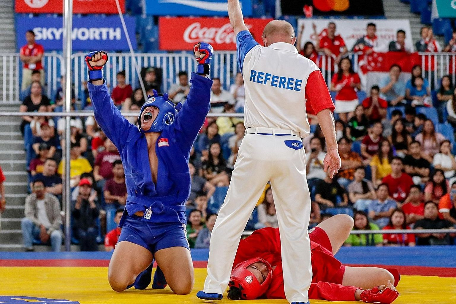Singapore's Nazri Sutari screaming in joy yesterday after beating Indonesia's Jason Sim in the SEA Games combat sambo under-82kg, in Angeles city.