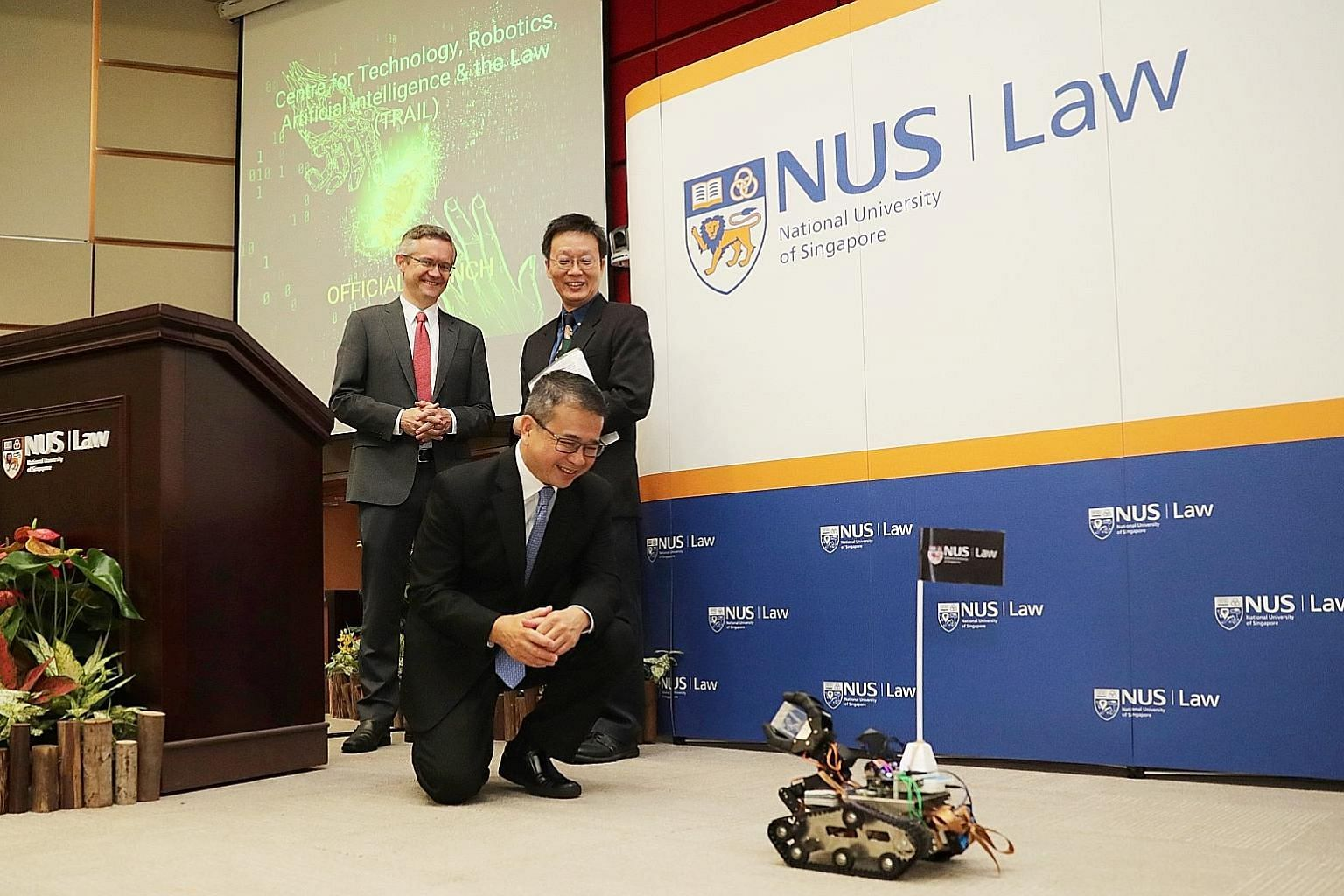 "Mobile robot ""Clair"" presenting a token of appreciation to Senior Minister of State for Law and Health Edwin Tong during the launch of the Centre for Technology, Robotics, Artificial Intelligence and the Law at NUS yesterday. With him are the centre'"