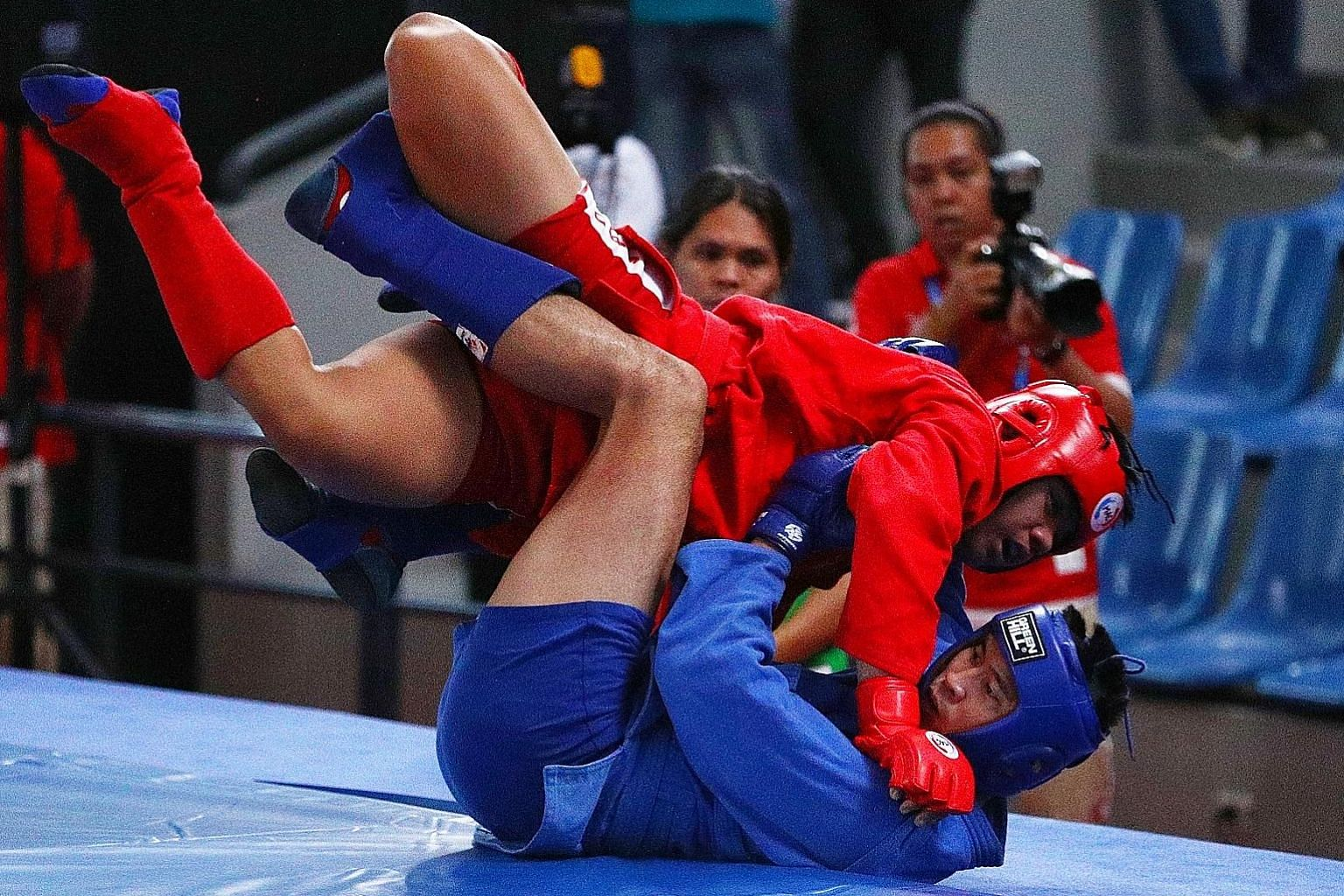 Singapore's Nazri Sutari on the attack against Indonesia's Jason Sim in the combat sambo Under-82kg final in Angeles yesterday.