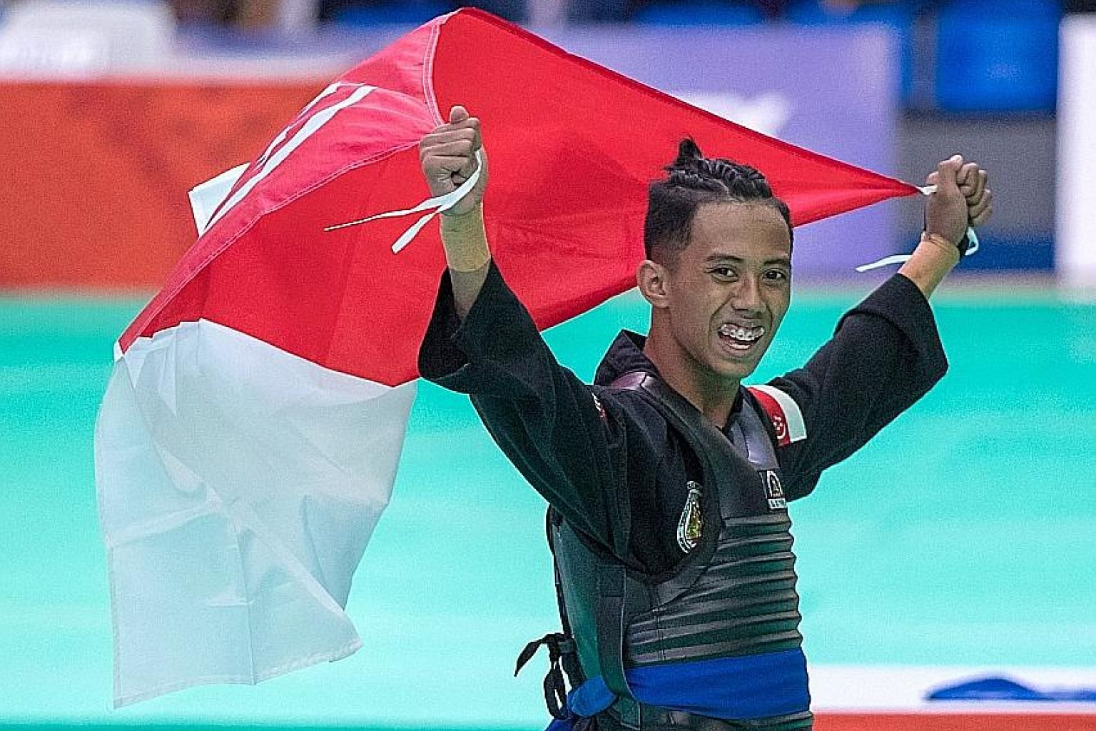 Singapore's Hazim Yusli celebrating his victory in the 50-55kg tanding (sparring) class yesterday. He got off to a shaky start in the final before beating Vietnam's Nguyen Dinh Tuan 4-1.