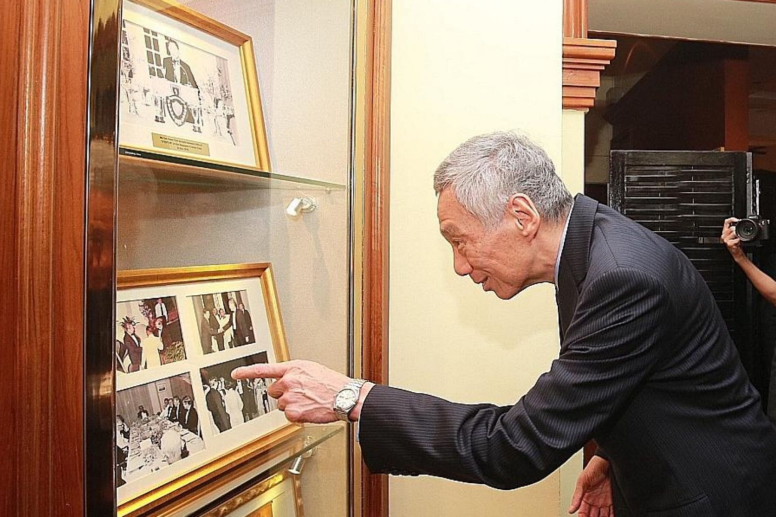 Prime Minister Lee Hsien Loong looking at photographs displayed at the Singapore Cricket Club which feature the late Mr Lee Kuan Yew. PM Lee was conferred the club's honorary title of Distinguished Visitor yesterday.