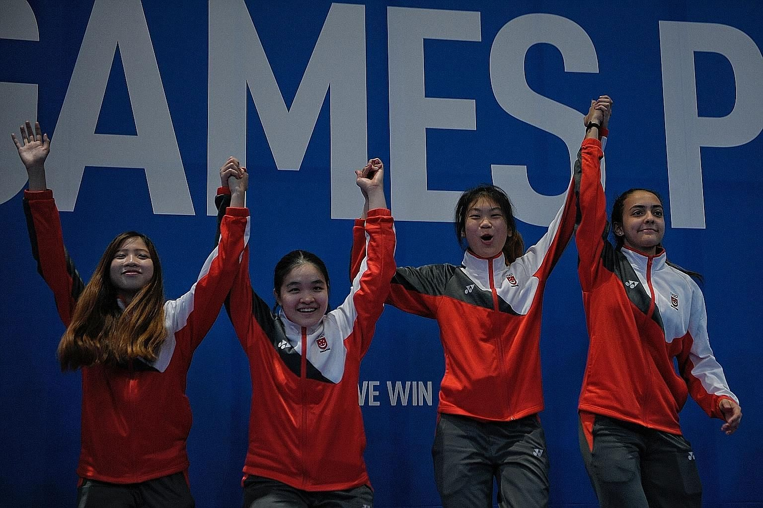 The victorious Singapore team of (from left) Tatiana Wong, Maxine Wong, Denyse Chan and Amita Berthier on the top step of the podium, after coming from behind to beat Vietnam in the SEA Games women's foil team final at the World Trade Centre in Manil
