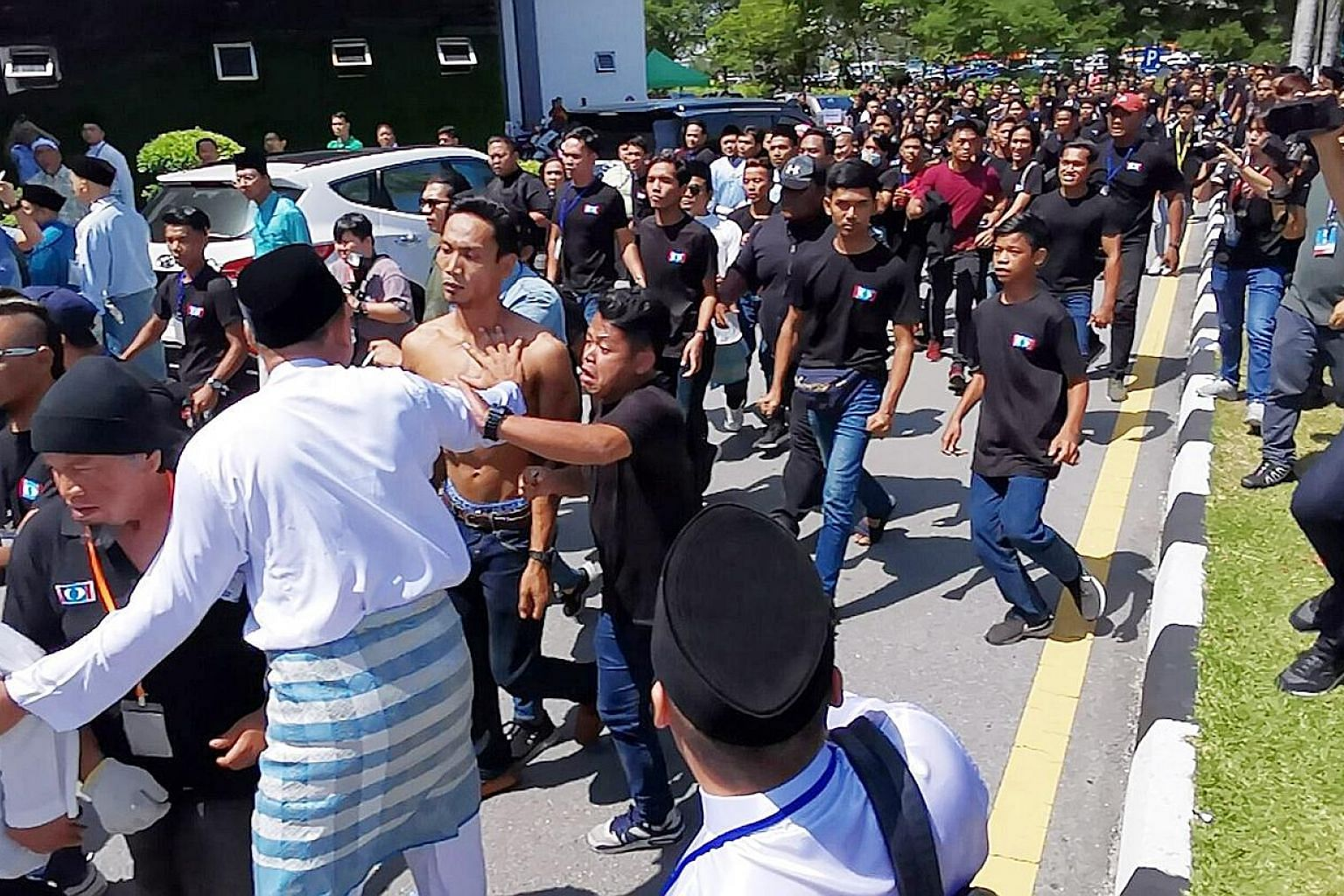 Scuffles broke out outside (above) and inside (below) the venue of the PKR's youth congress in Melaka yesterday morning, leading the pro-Azmin delegates in blue to skip the rest of the meet. A group of youths clad in black were seen at the Parti Kead