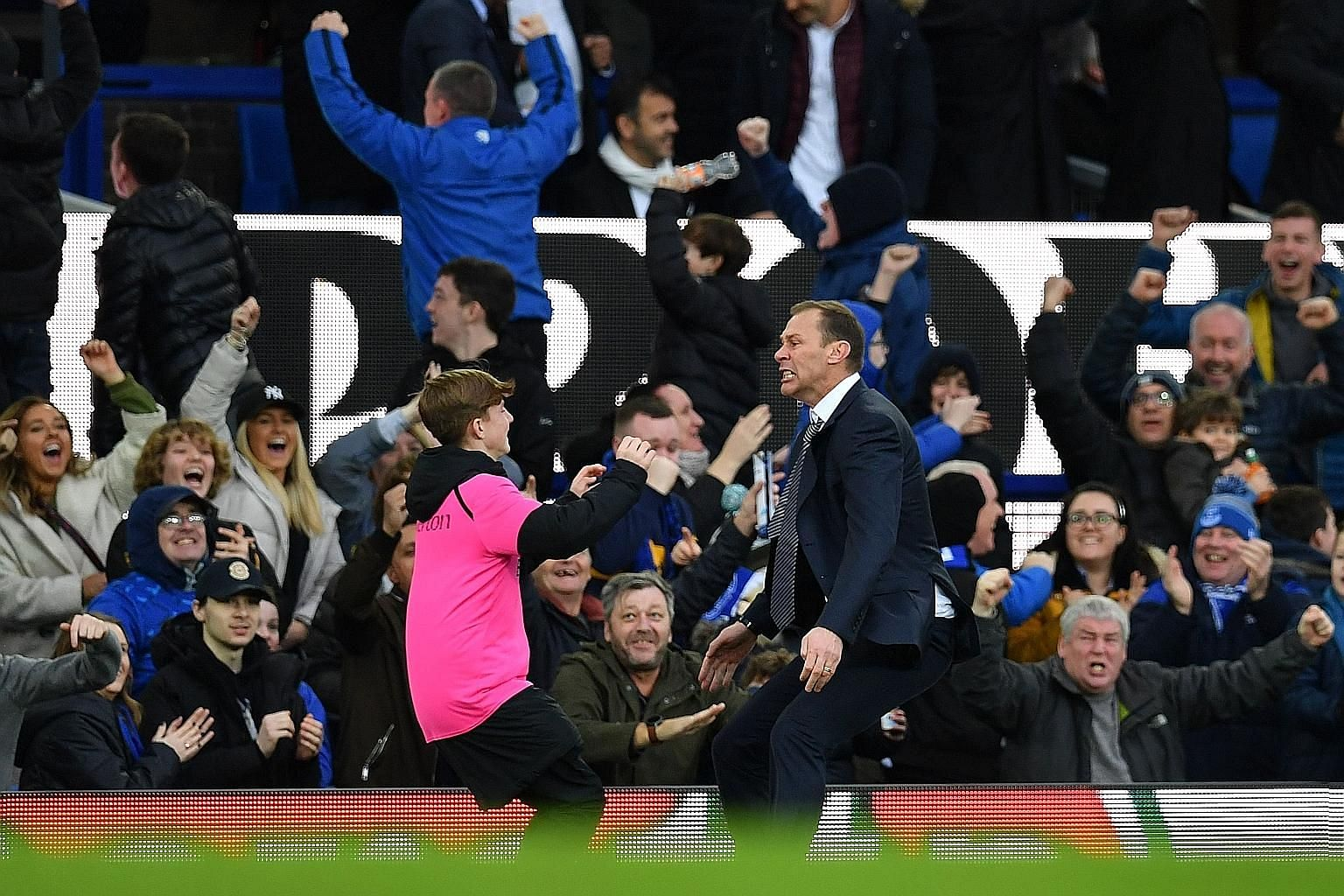 Everton's caretaker manager Duncan Ferguson running to embrace a ballboy, as he celebrates after striker Dominic Calvert-Lewin netted the final goal in their 3-1 Premier League win over Chelsea at Goodison Park yesterday