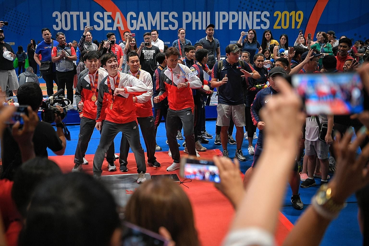 (Above) The Singapore men's foil team getting into the groove with other teams and fans after the medal presentation at Manila's World Trade Centre yesterday. Left: Joshua Lim roaring after a good showing.