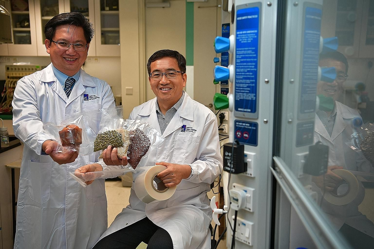 A 2017 photo showing Dou Yee Enterprises vice-president Alex Tan (left) and A*Star scientist Li Xu with examples of food stored in smart packaging, which was developed with A*Star scientists. The firm has gained from FTAs like those covering US-Singa