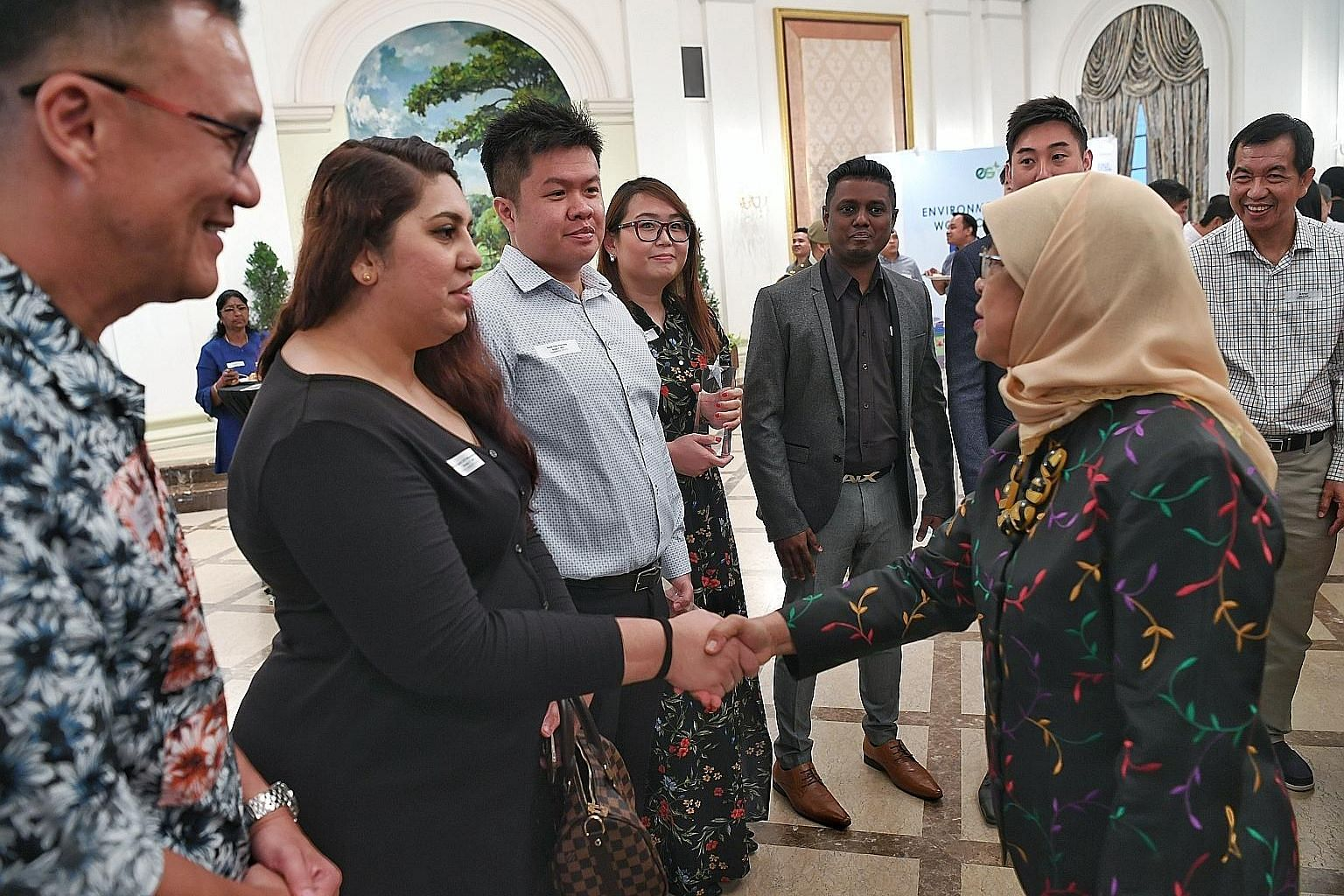 President Halimah Yacob meeting guests and award winners - including Ms Regina Cheah (fourth from left), who received an Environmental Services Star Award - at the Istana yesterday.
