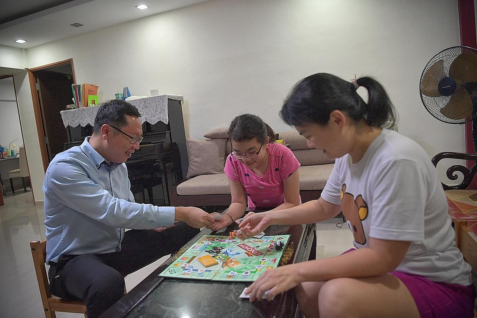Mr Teo Cher Hwa and his wife, Ms Chew Chiou Pyng, playing Monopoly with their daughter Poh Huan at home. Mr Teo says playing a traditional board game like Monopoly is an excellent way to introduce their two children to the property market and how to