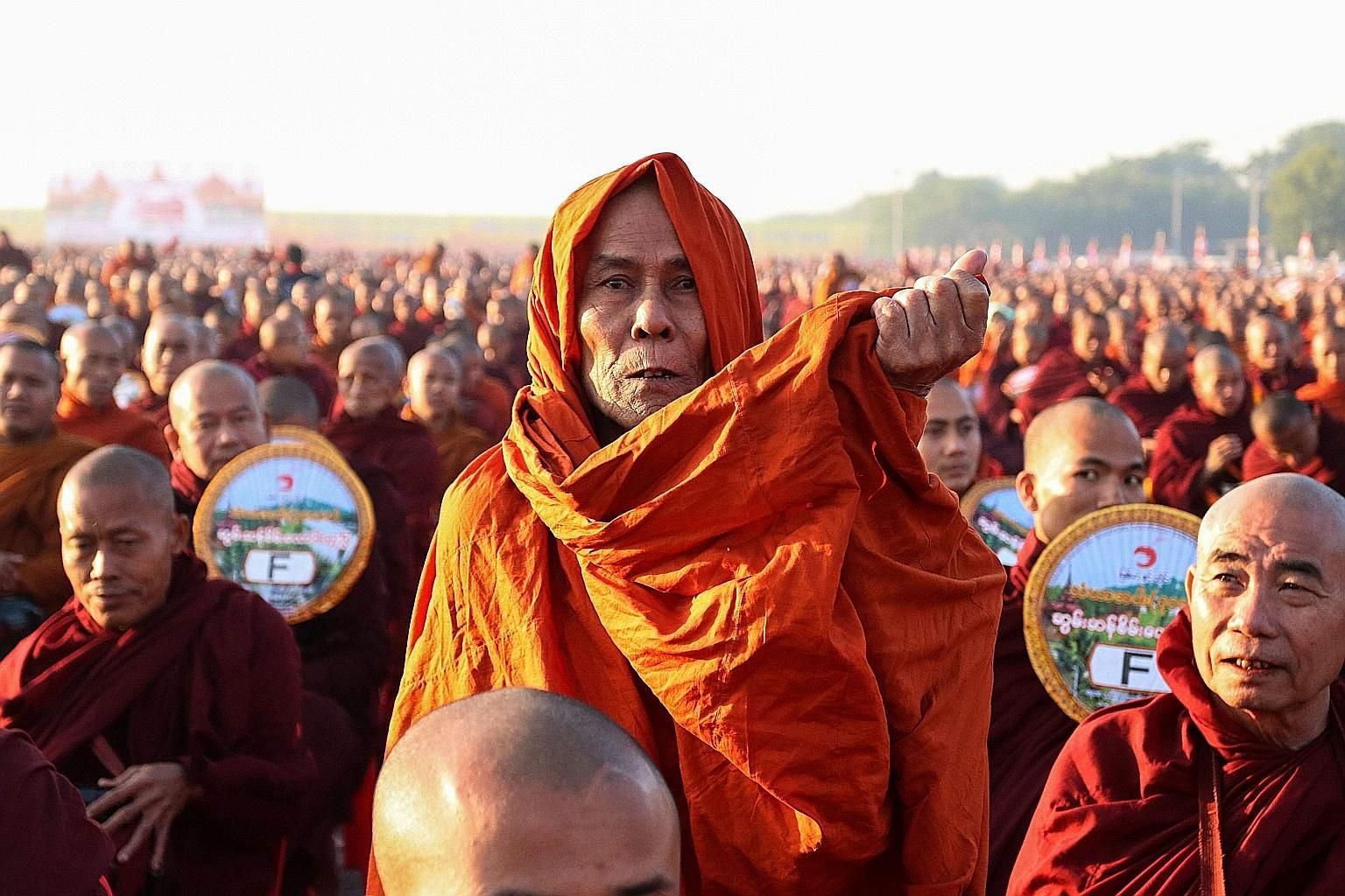 Monks lining up for alms during an alms-giving ceremony yesterday that was partly organised by the Thailand-based Dhammakaya foundation. Thirty thousand monks assembled in the early morning chill next to an airport in the central city of Mandalay, a