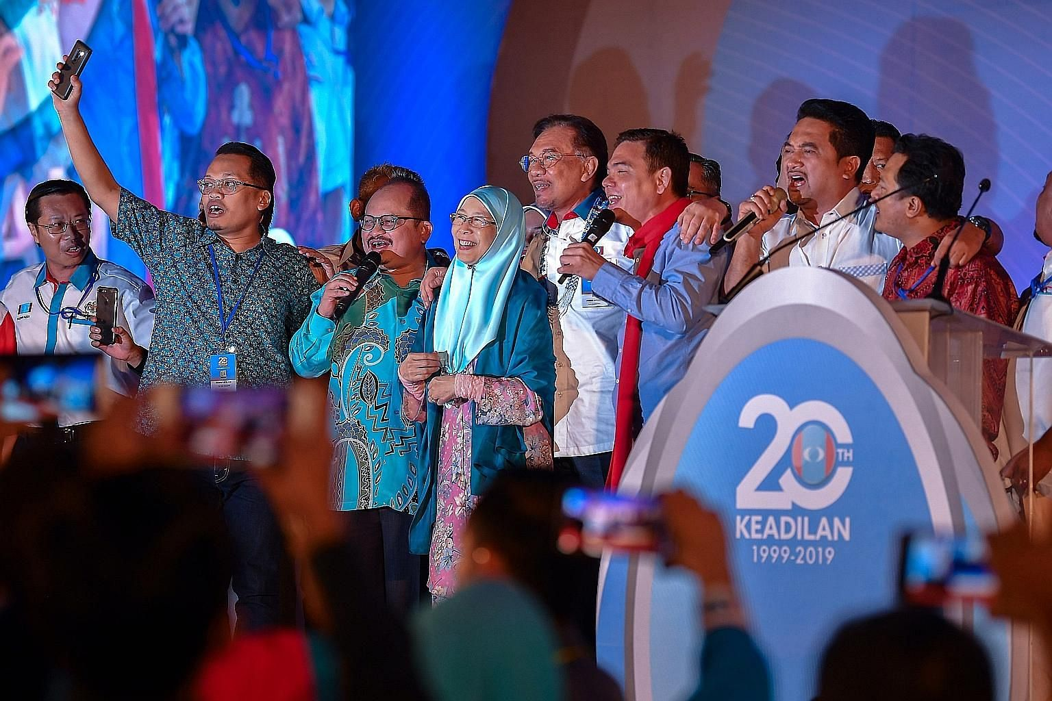 Parti Keadilan Rakyat president Anwar Ibrahim (centre, in white) with his faction's leadership team singing at the end of the party's annual congress in Melaka state. With him is his wife and chairman of PKR's board of advisers, Datuk Seri Wan Azizah