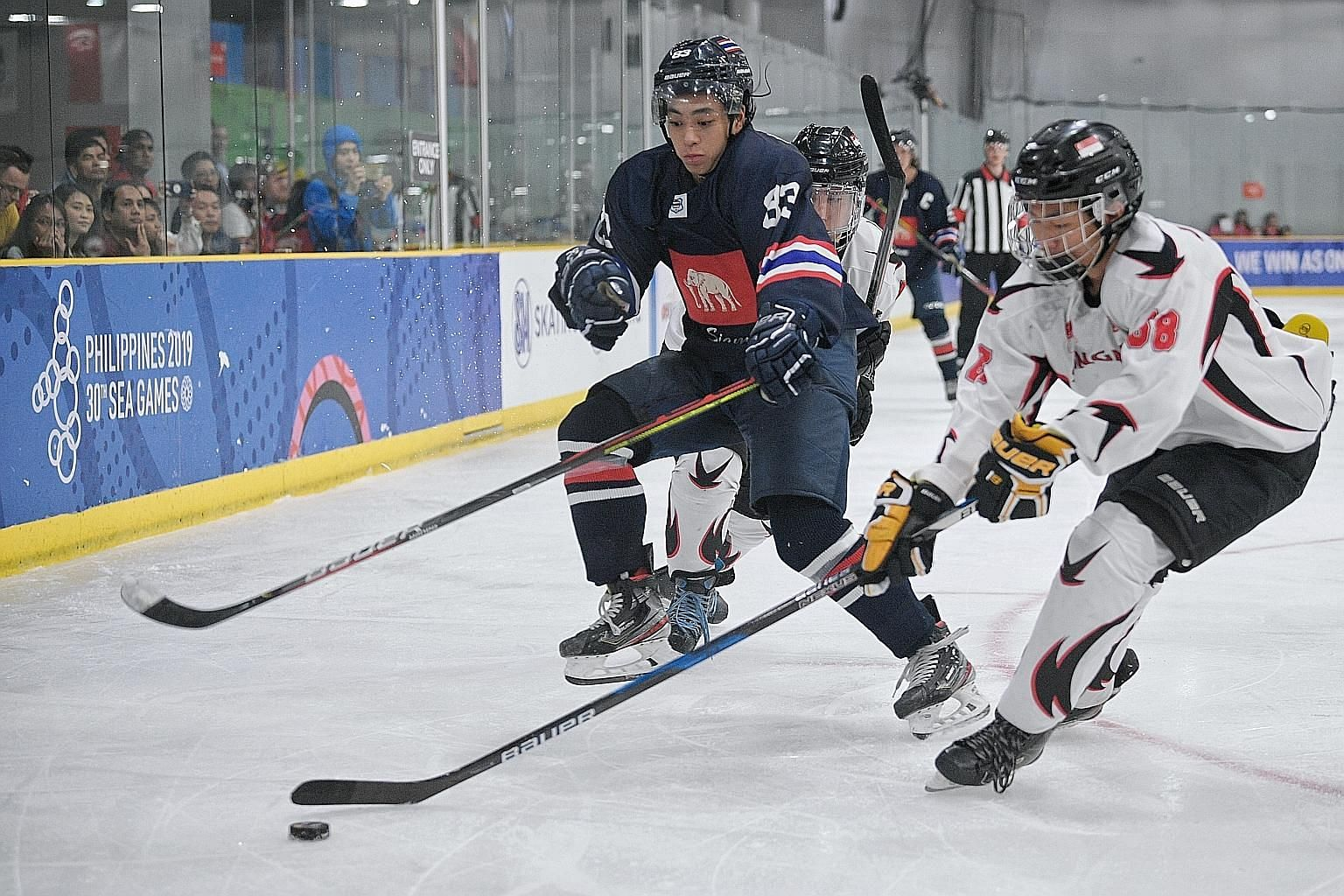 Singapore's Ryan Tan and Thailand's Masato Kitayama tussling for the puck in the SEA Games ice hockey final. Thailand had 55 shots on goal in the 8-0 win.
